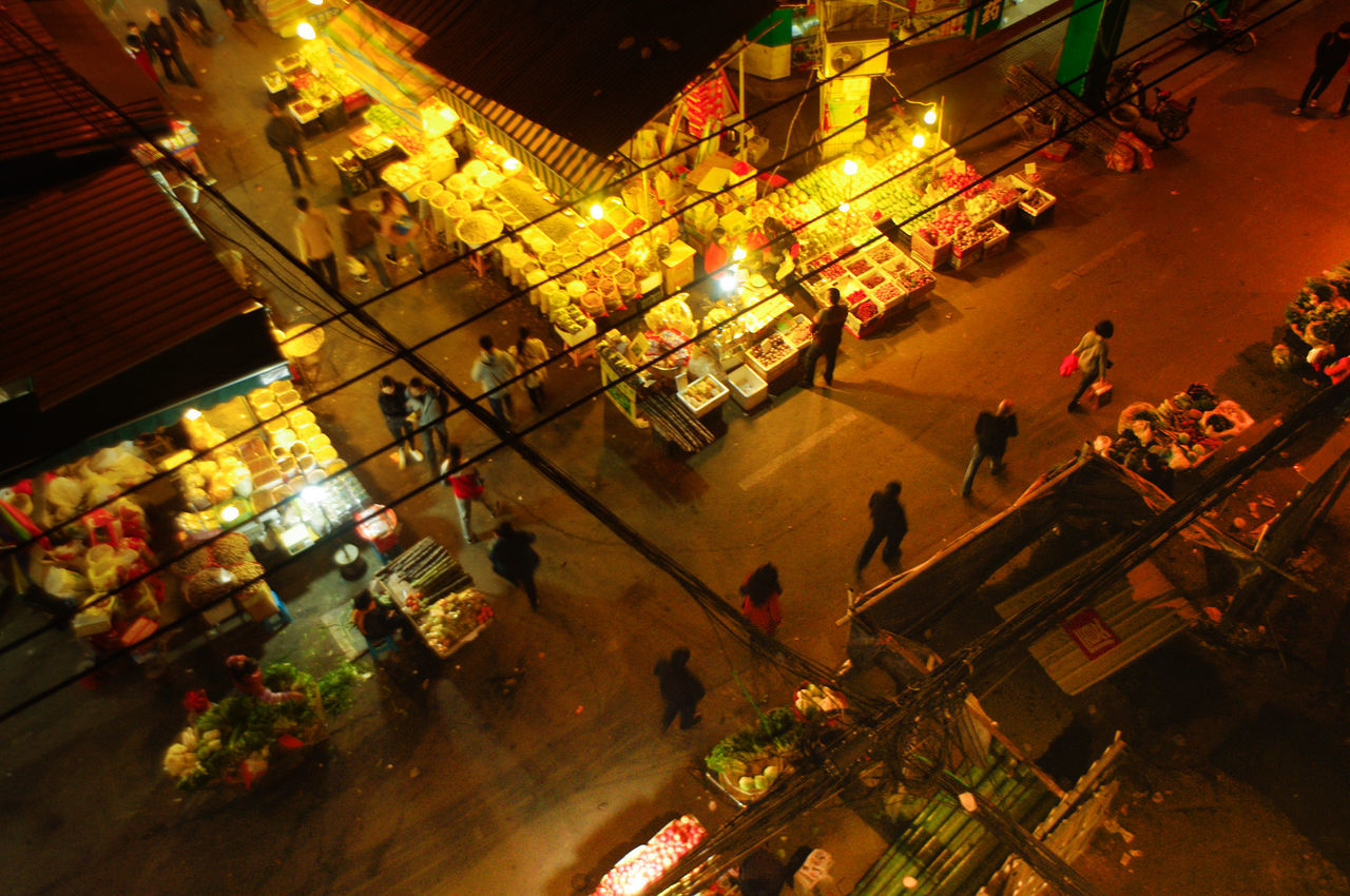 High Angle View Of People By Stores At Night