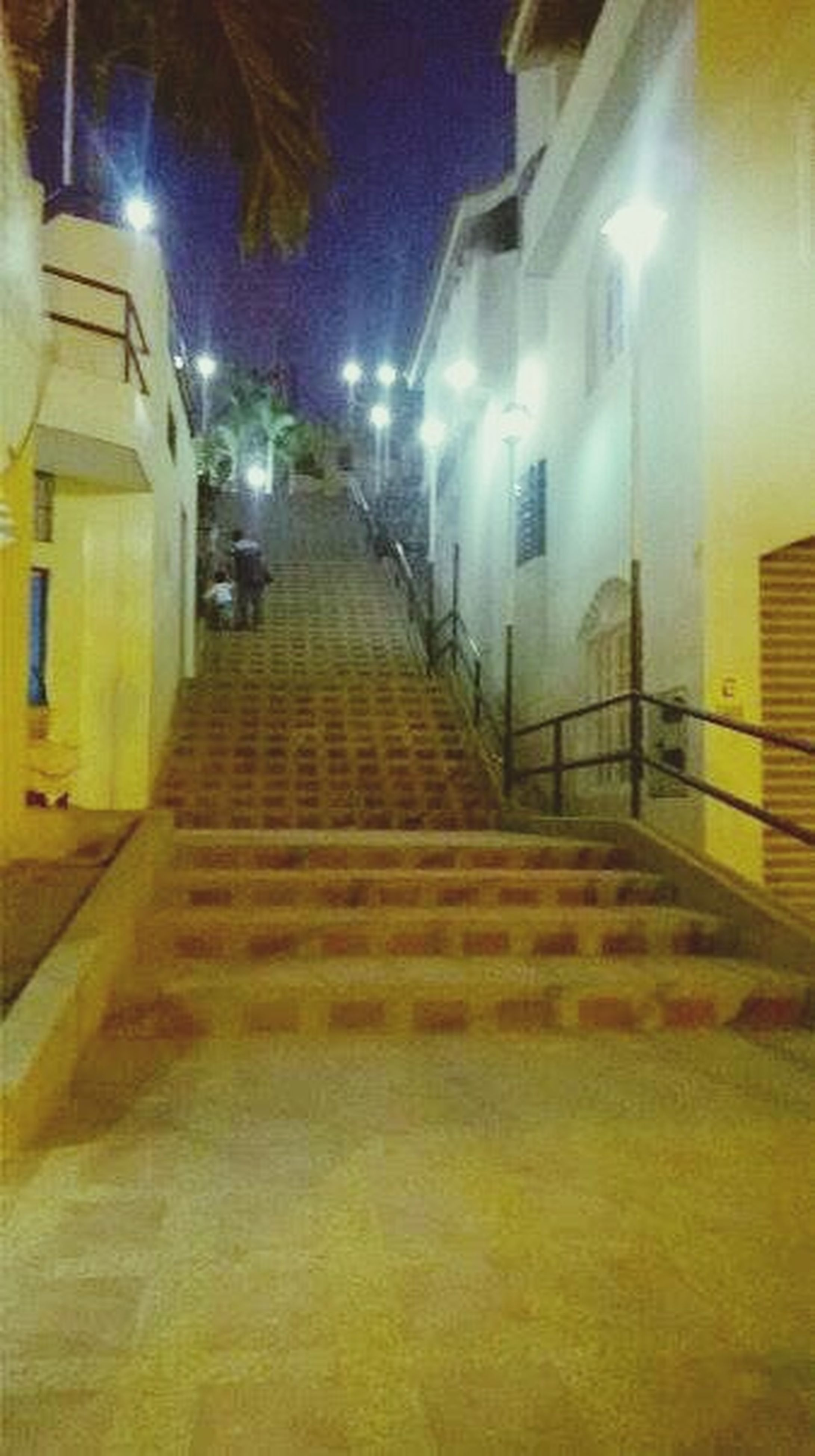 illuminated, architecture, built structure, the way forward, indoors, building exterior, night, lighting equipment, building, steps, wall - building feature, diminishing perspective, light - natural phenomenon, steps and staircases, corridor, empty, electric light, staircase, city, narrow