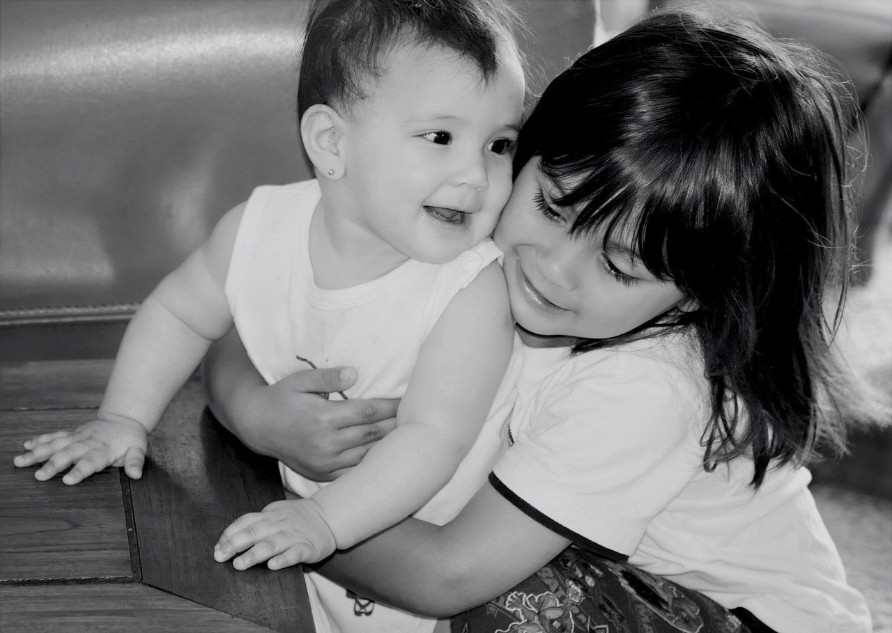 Girl Hugging Brother By Table