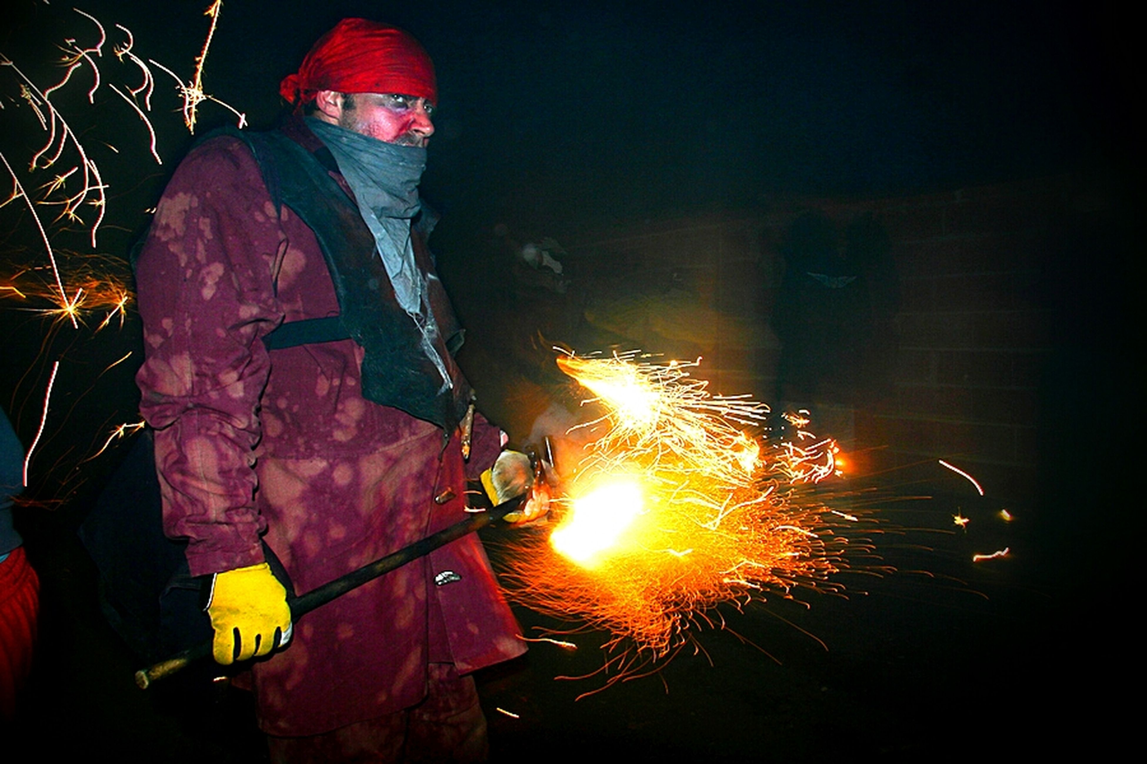night, lifestyles, men, leisure activity, illuminated, red, rear view, arts culture and entertainment, outdoors, celebration, holding, fire - natural phenomenon, motion, orange color, glowing, burning, standing