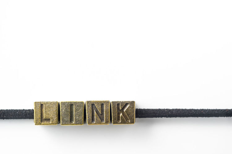 "Design concept - top view of metal cube word "" link "" link with line, isolated on white background Close-up Communication Copy Space Freshness Link, Business, Social, Web, Information, Iot, Internet, Community, Cable, World, Network, Isolated, White, Background, Line, Wire, Metal, Retro, Rustic, Shape, Shiny, Vintage, Copper, Cube, Necklace, Bracelet, Leather, Rope, Connect, Connection, Together No People Single Word Studio Shot Sweet Food Text White Background Wood - Material"