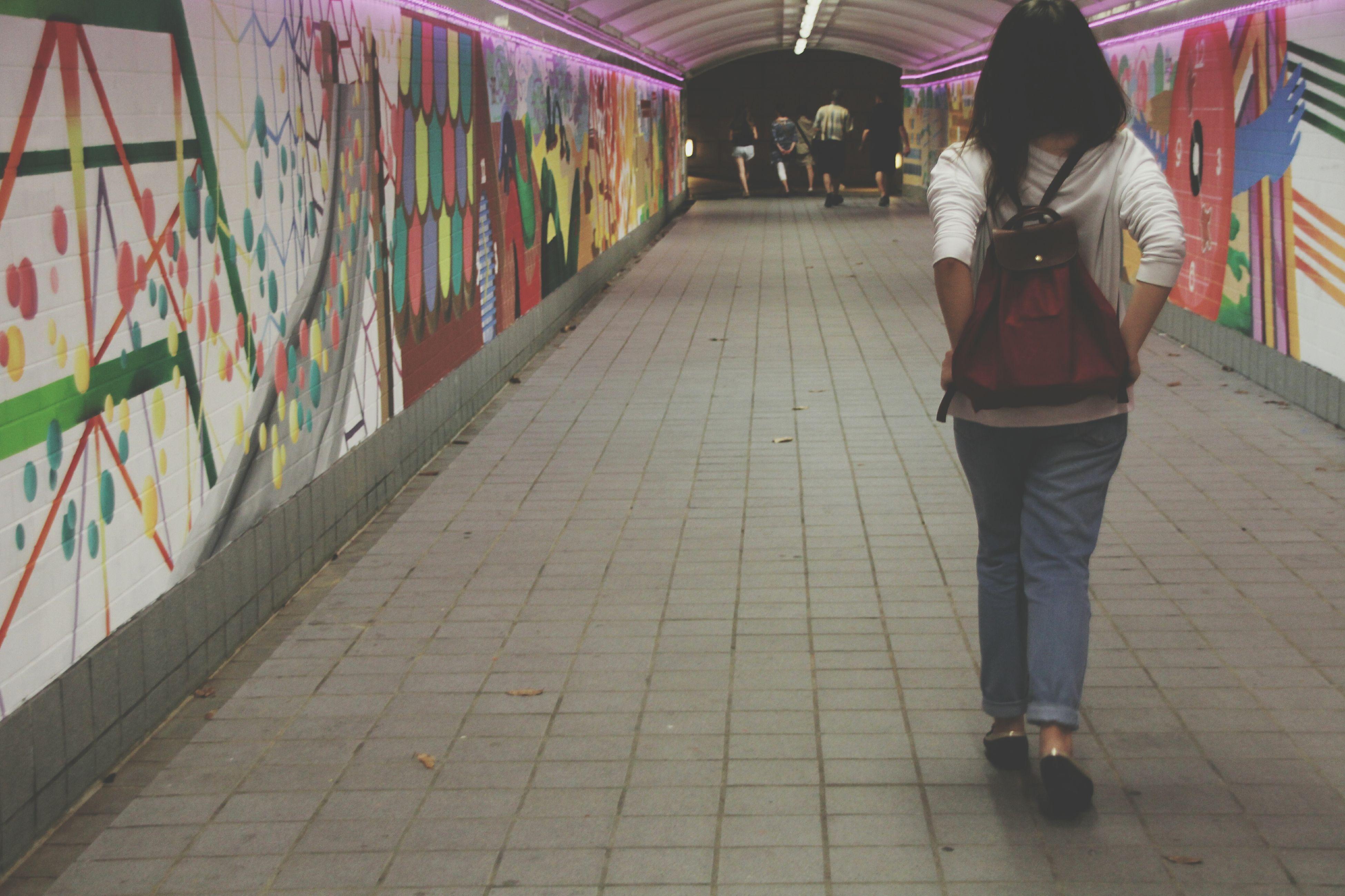 lifestyles, full length, leisure activity, the way forward, flooring, casual clothing, city life, illuminated, corridor, walkway, day, diminishing perspective, tile