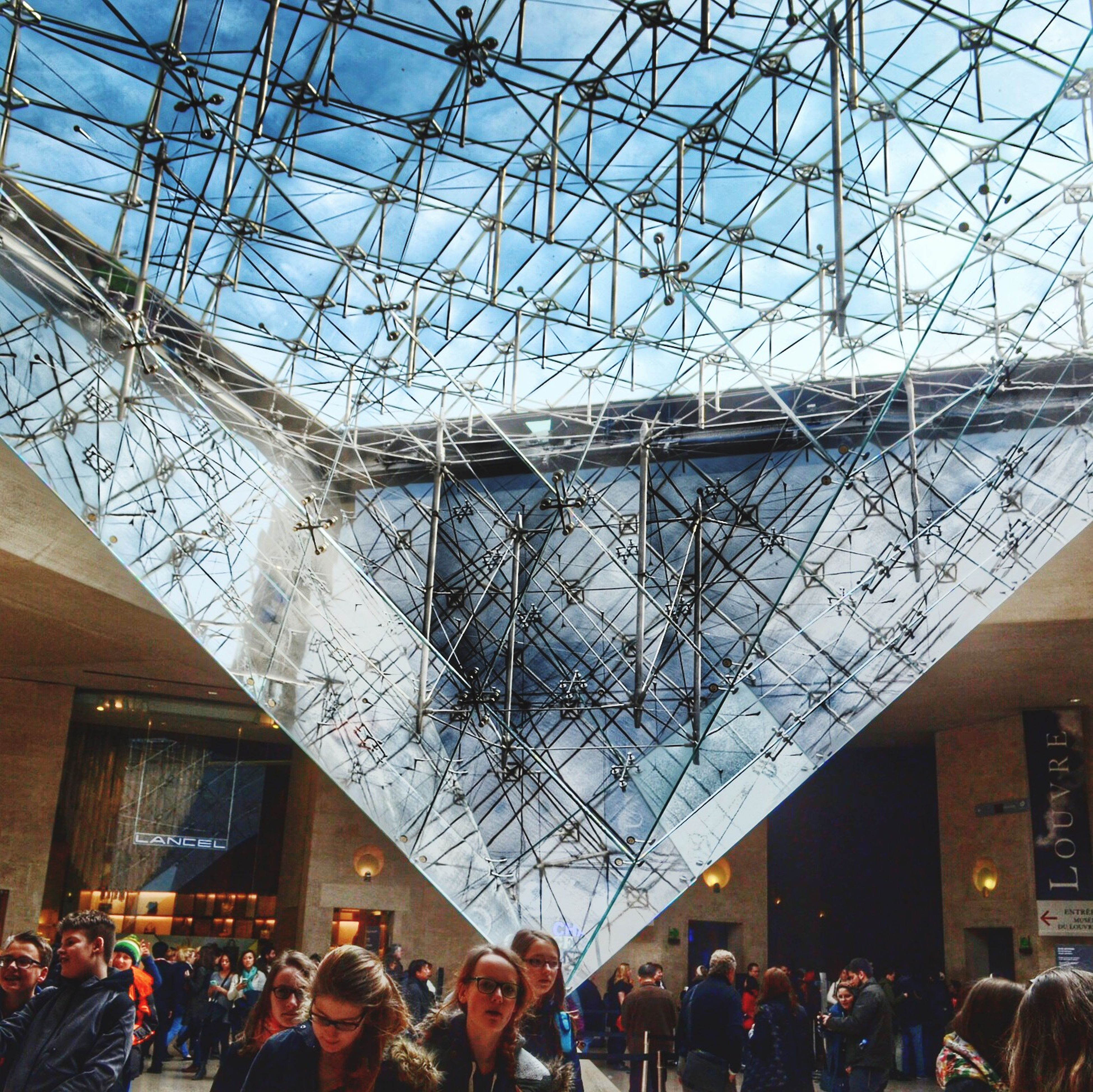 indoors, large group of people, lifestyles, men, ceiling, person, leisure activity, built structure, architecture, crowd, glass - material, low angle view, shopping mall, hanging, transparent, day, arts culture and entertainment, lighting equipment, illuminated