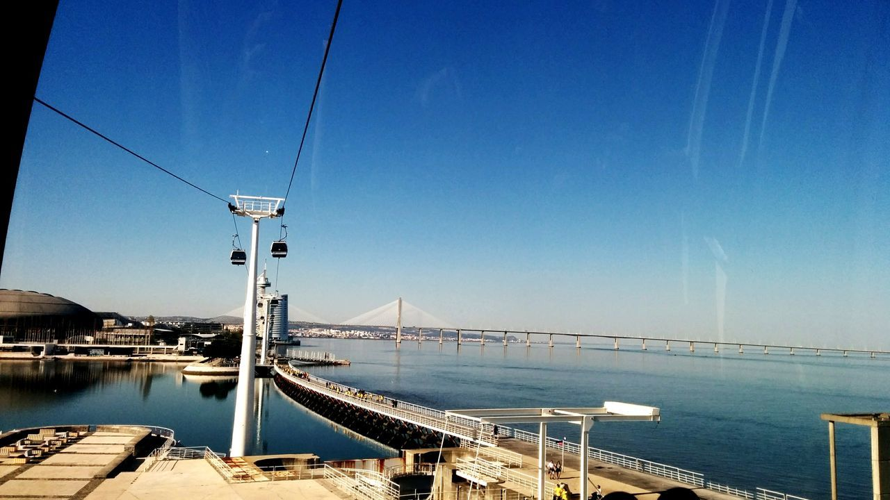 connection, transportation, water, blue, built structure, architecture, bridge - man made structure, cable, no people, day, outdoors, sky, sea, clear sky, scenics, nautical vessel, nature, city, building exterior