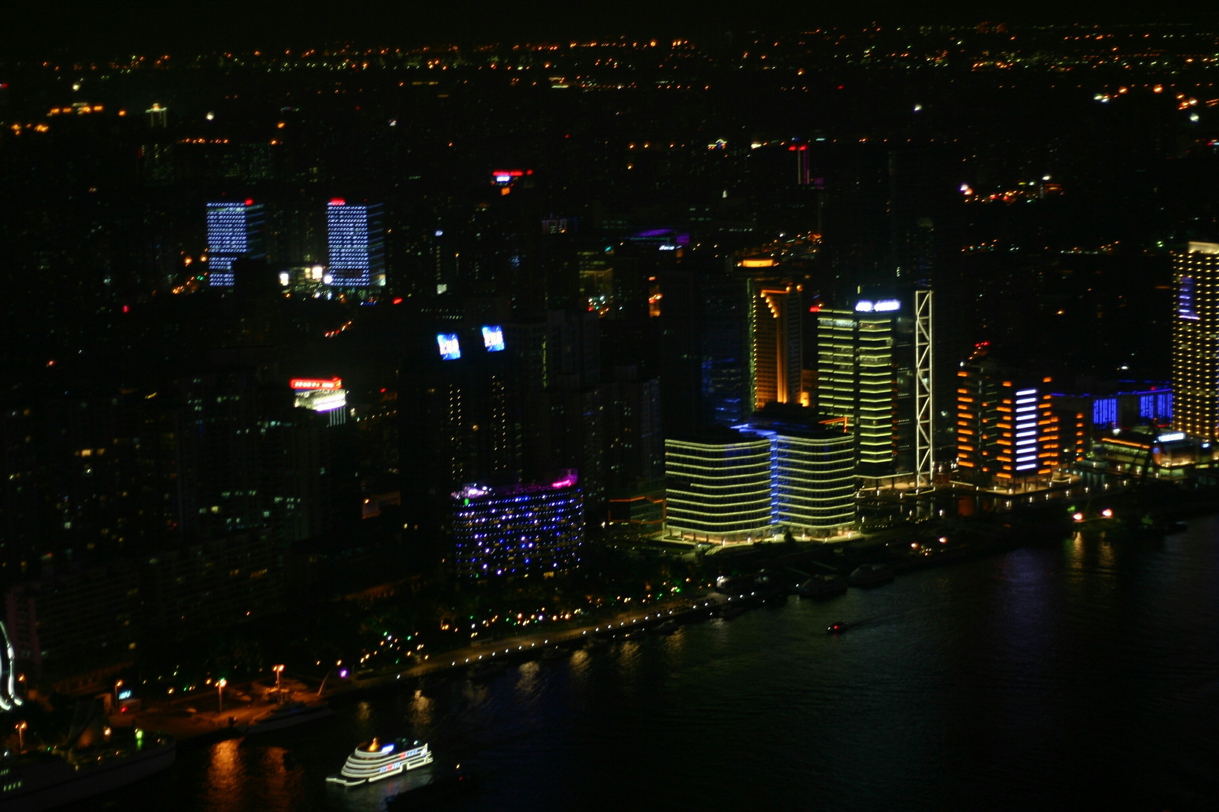 illuminated, night, city, building exterior, cityscape, architecture, built structure, skyscraper, water, crowded, reflection, river, waterfront, residential district, residential building, modern, office building, city life, high angle view, residential structure