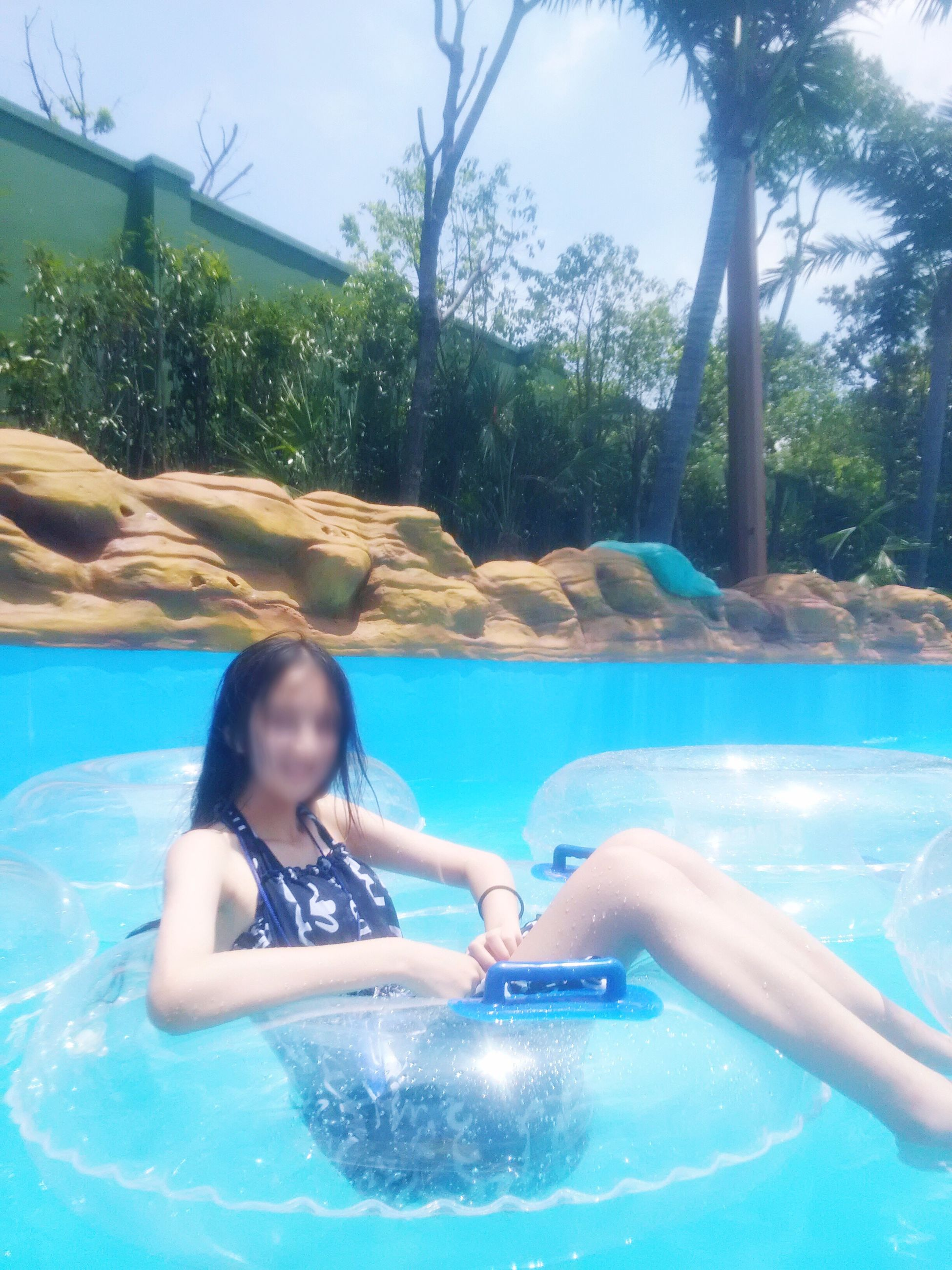 swimming pool, water, leisure activity, real people, tree, day, one person, lifestyles, fun, outdoors, enjoyment, sunlight, swimming, happiness, vacations, young women, summer, young adult, relaxation, smiling, nature, sky, people