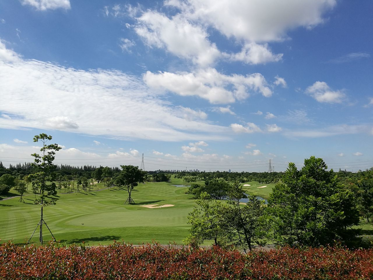 Scenic View Of Golf Course Against Cloudy Sky