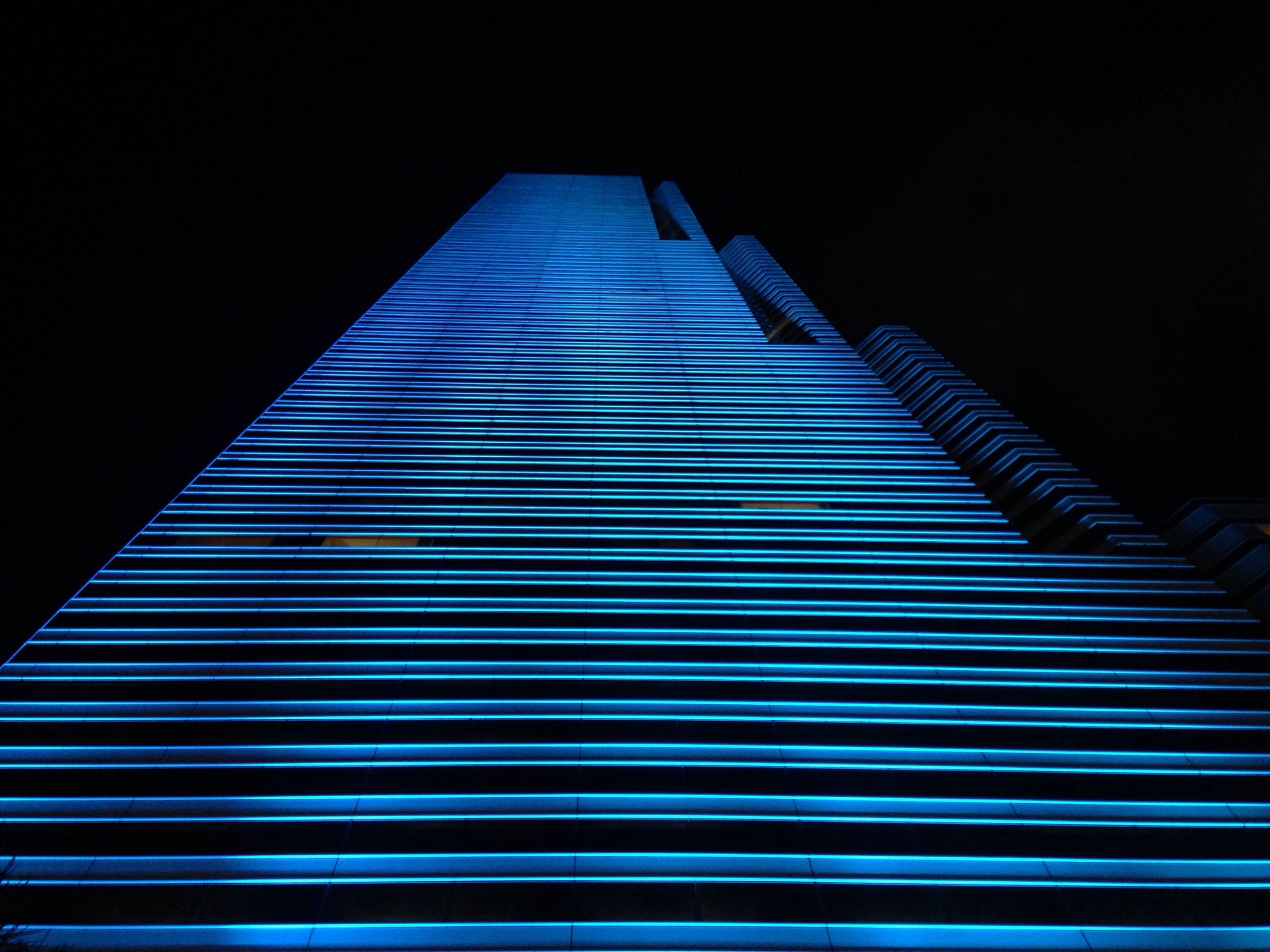 low angle view, architecture, building exterior, built structure, modern, skyscraper, office building, tall - high, night, city, illuminated, pattern, clear sky, building, blue, sky, no people, tower, outdoors, tall