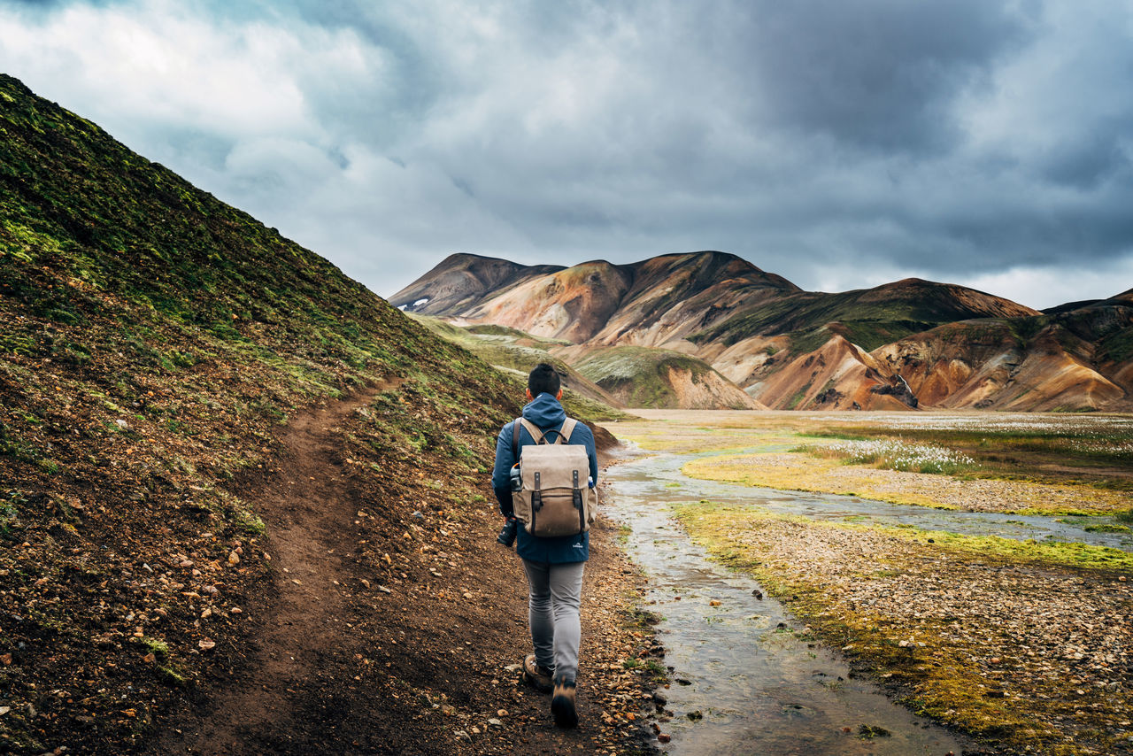 Hiker Walking On Pathway By Field Against Mountains And Cloudy Sky