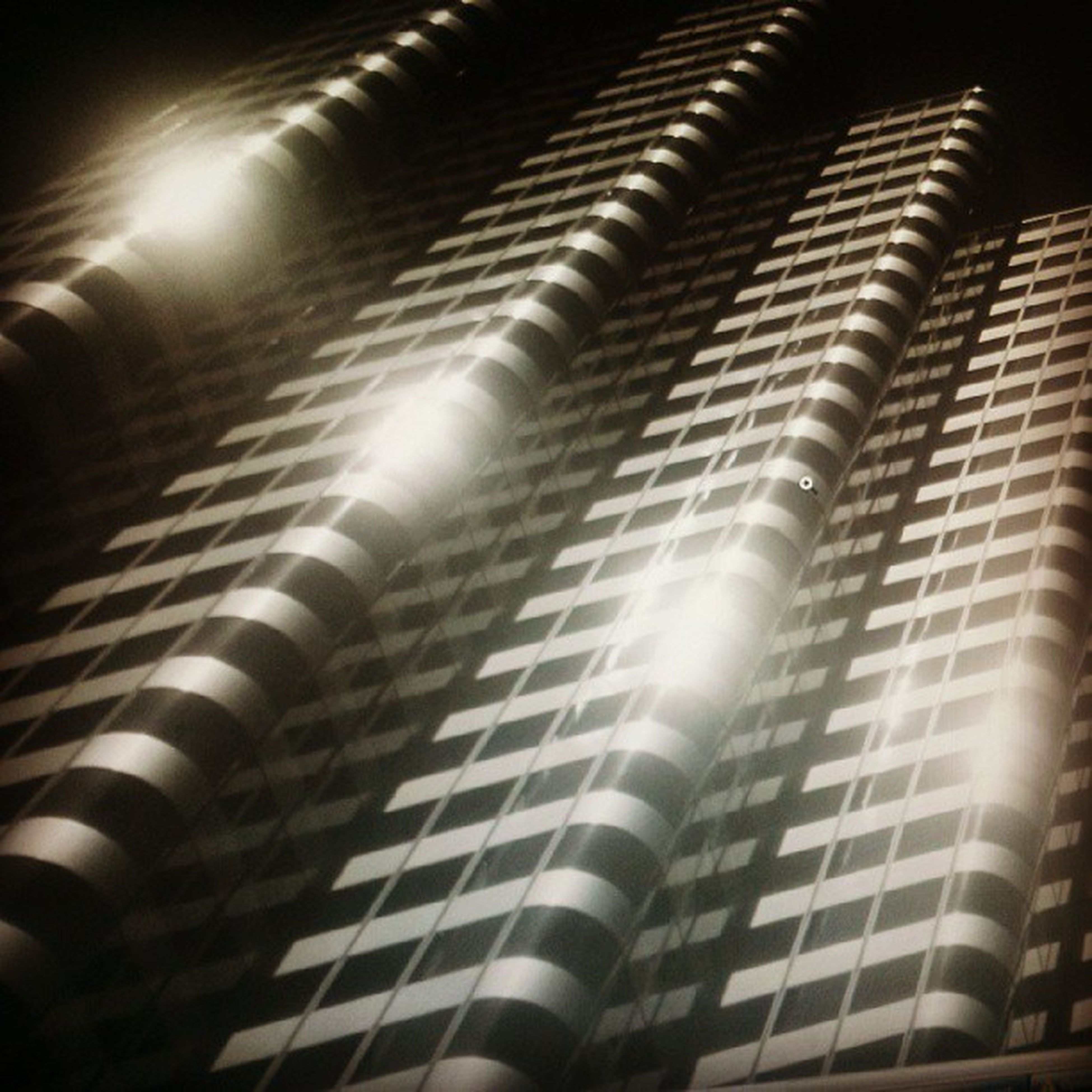 architecture, built structure, indoors, low angle view, pattern, repetition, building exterior, illuminated, night, metal, in a row, modern, architectural feature, building, no people, metallic, factory, industry, design, close-up