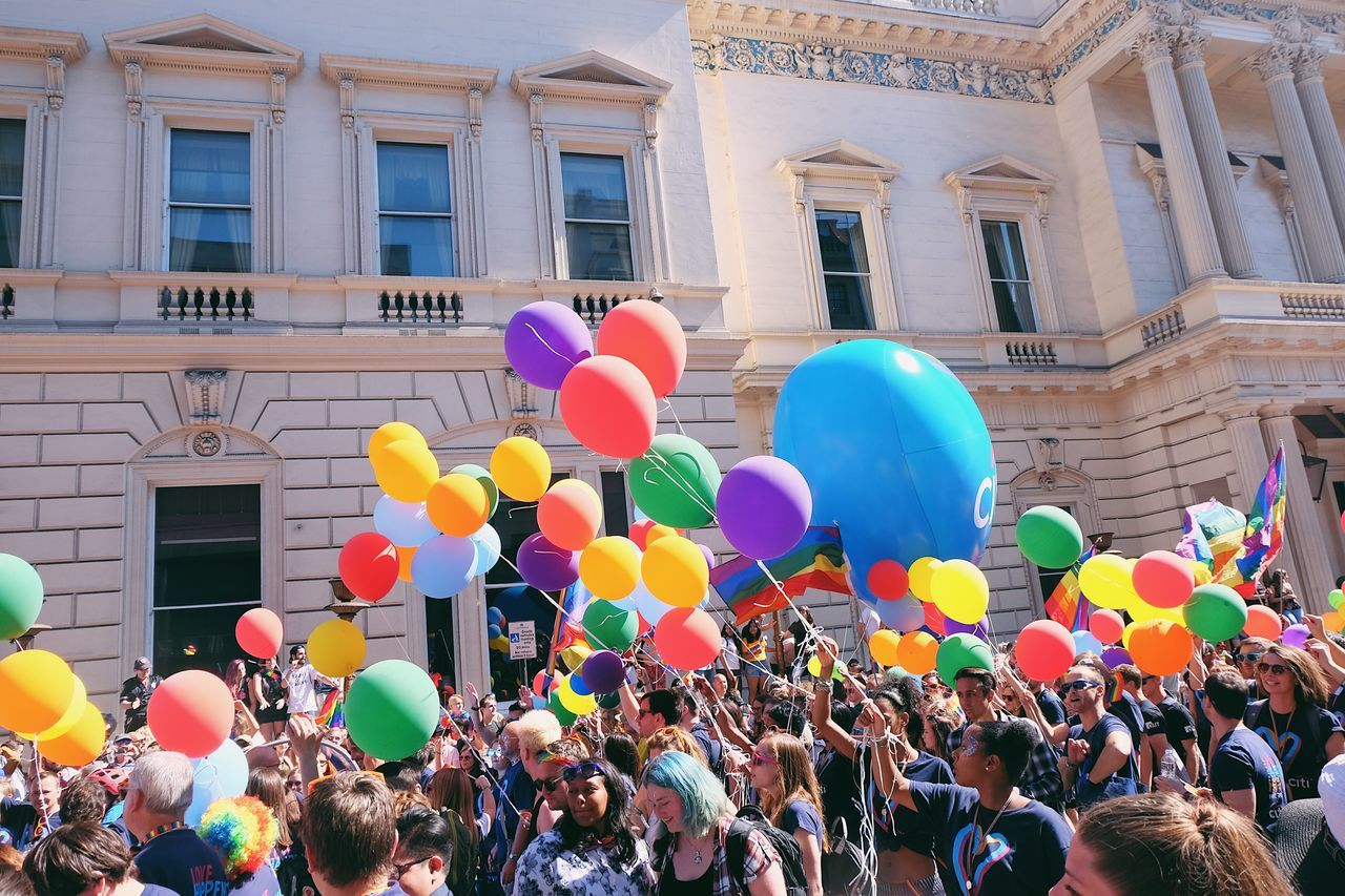 balloon, building exterior, celebration, large group of people, architecture, helium balloon, real people, built structure, multi colored, men, fun, women, outdoors, crowd, day, togetherness, lifestyles, happiness, city, people
