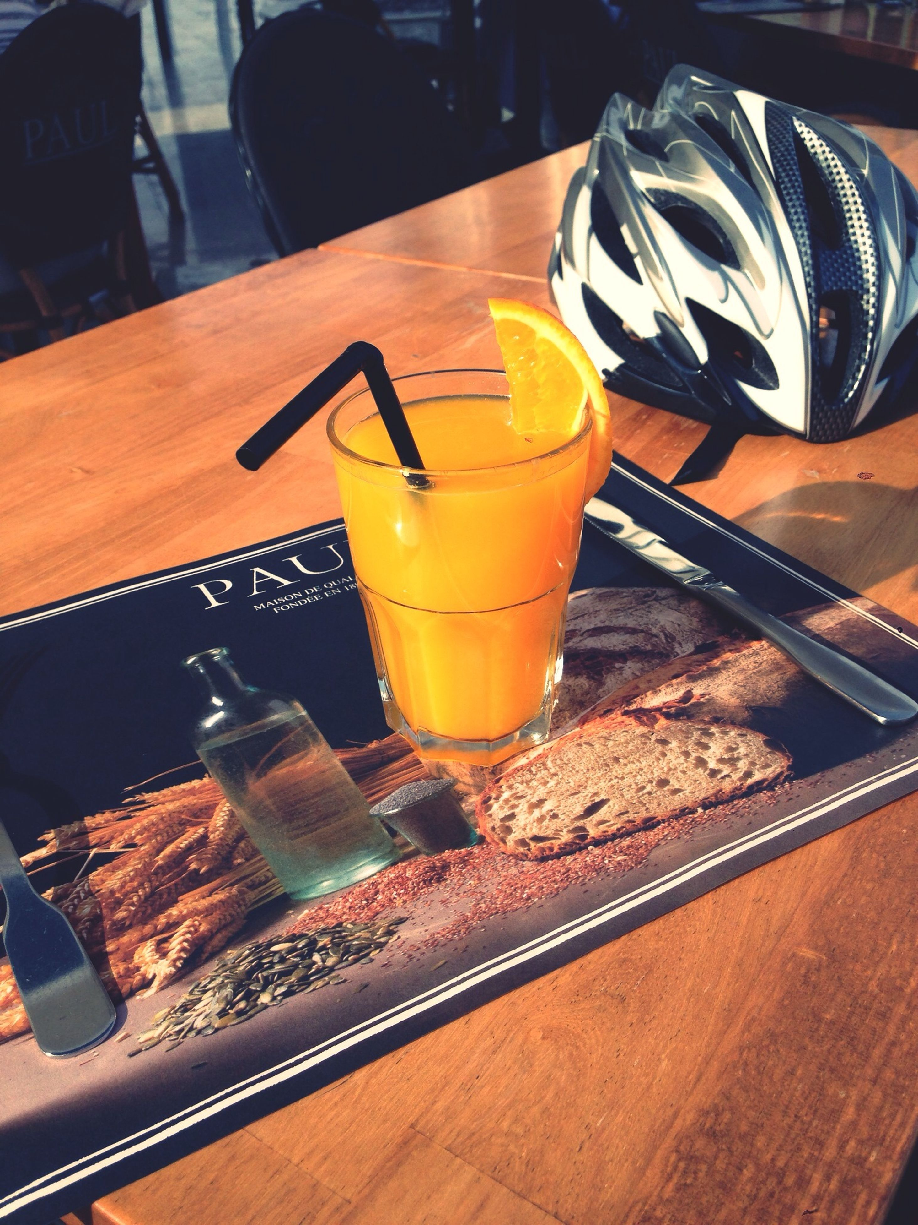 food and drink, indoors, table, drink, freshness, still life, refreshment, close-up, drinking glass, yellow, high angle view, wood - material, glass - material, no people, restaurant, focus on foreground, orange color, drinking straw, alcohol, food