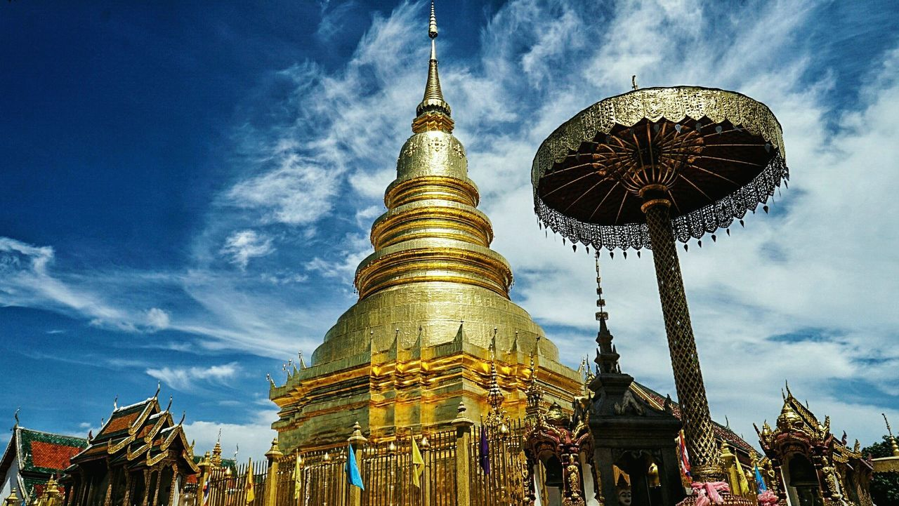 Architecture Building Exterior Spirituality Built Structure Low Angle View Religion Sky Place Of Worship Gold Colored Cloud Blue Spire  Cloud - Sky Temple - Building Gold Travel Destinations Famous Place Outdoors Tourism Wat Haripunchai Lanna Lan Na