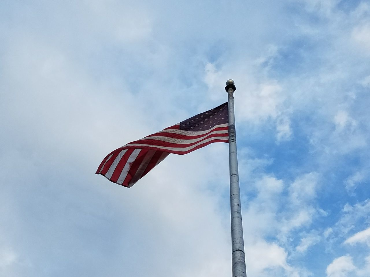 patriotism, flag, low angle view, striped, stars and stripes, flag pole, sky, no people, red, day, pride, outdoors
