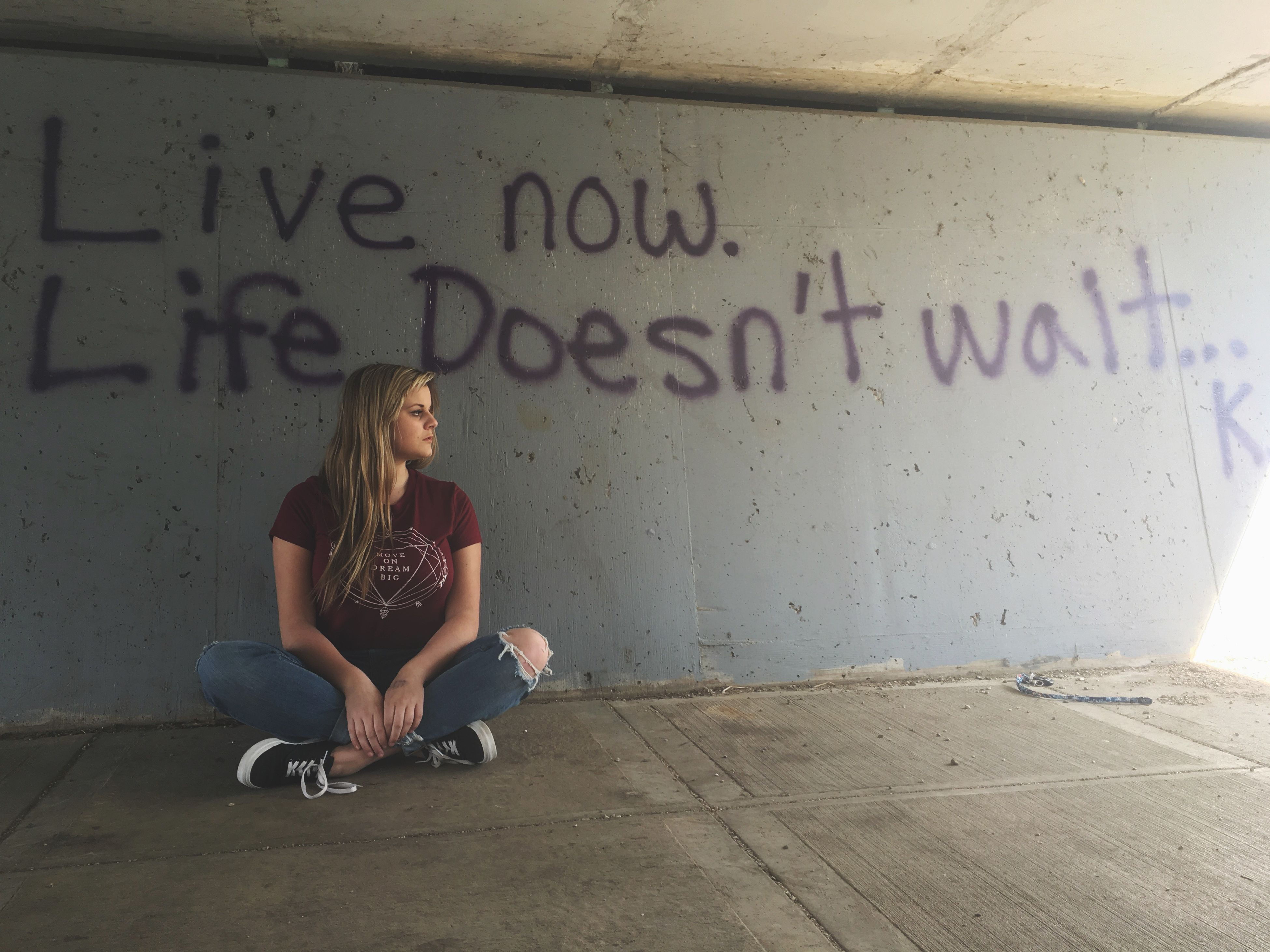 lifestyles, casual clothing, full length, leisure activity, text, communication, wall - building feature, young adult, standing, person, western script, graffiti, young women, front view, street, men, architecture