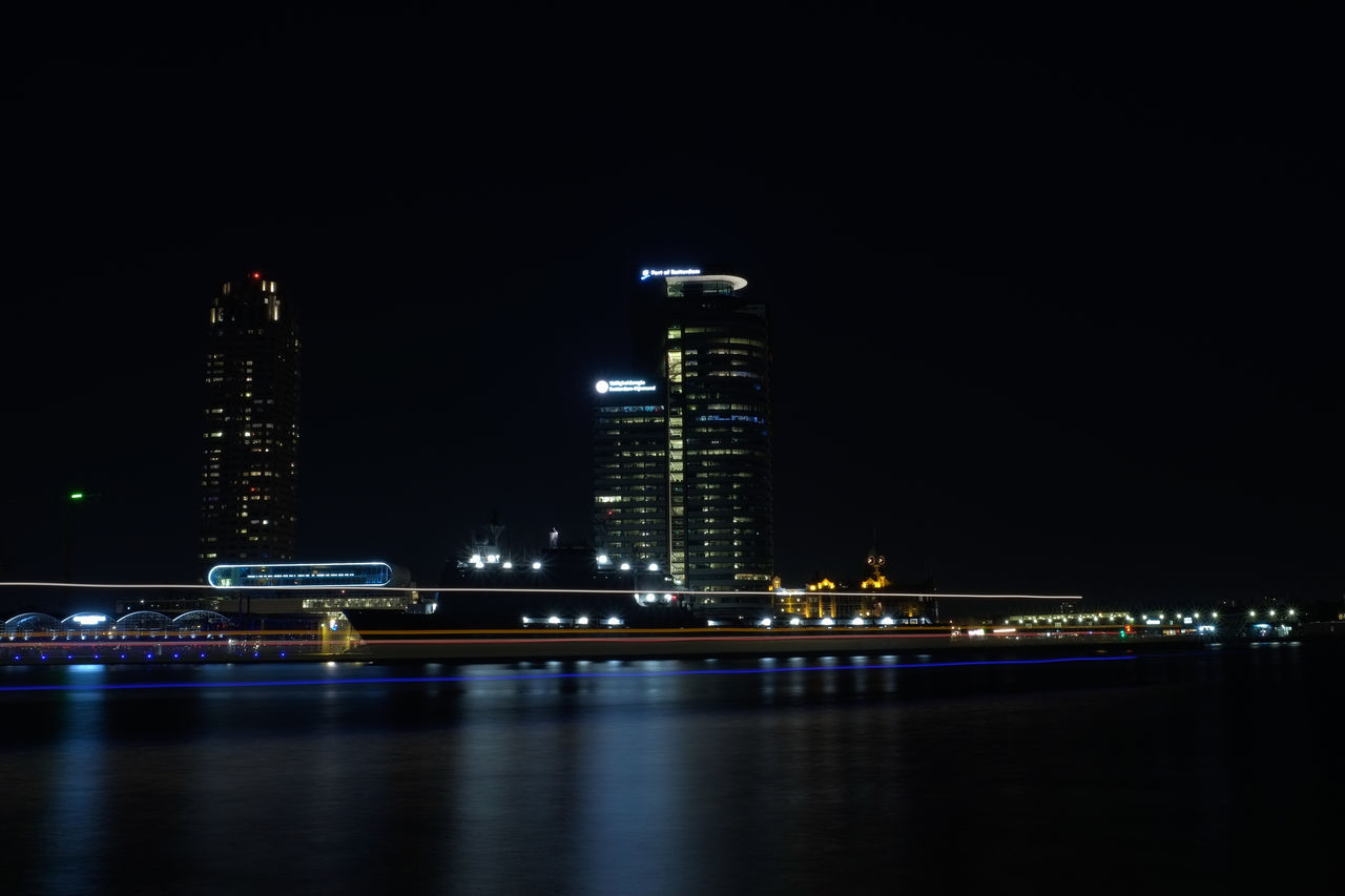 illuminated, night, architecture, building exterior, skyscraper, built structure, modern, city, tall - high, waterfront, tower, travel destinations, river, cityscape, reflection, water, urban skyline, downtown district, no people, clear sky, outdoors, sky