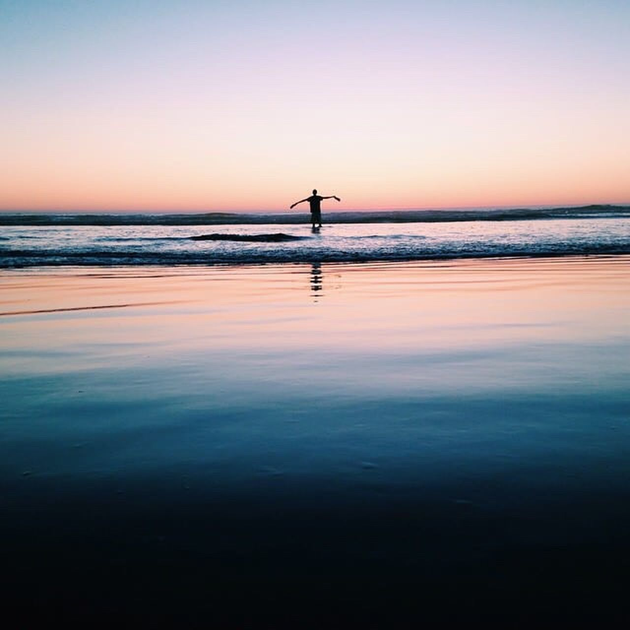 sunset, silhouette, reflection, beauty in nature, sky, nature, sea, scenics, water, orange color, tranquil scene, horizon over water, tranquility, one person, full length, blue, outdoors, day, people, adult