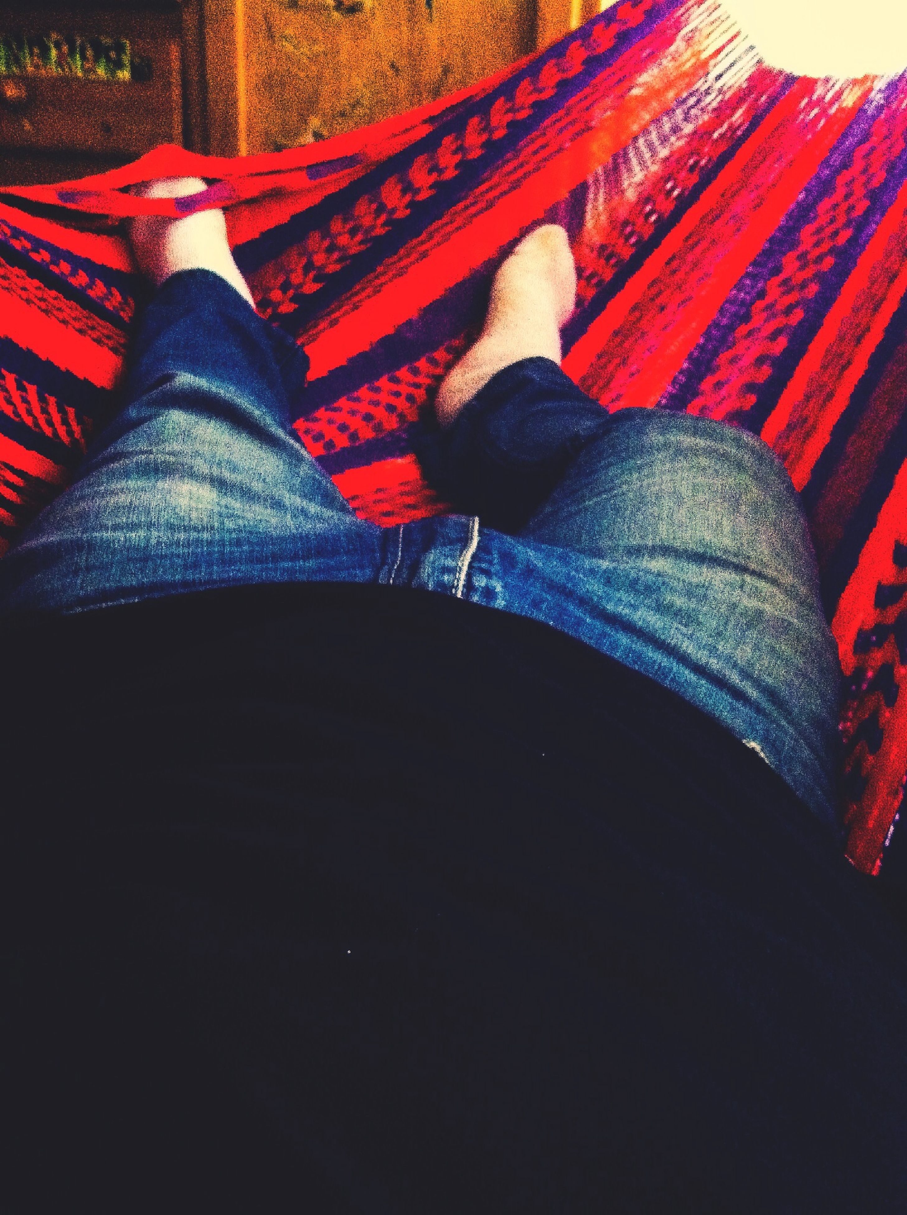 red, indoors, low section, sitting, relaxation, person, lifestyles, high angle view, casual clothing, men, leisure activity, resting, standing, striped, jeans, comfortable, rear view