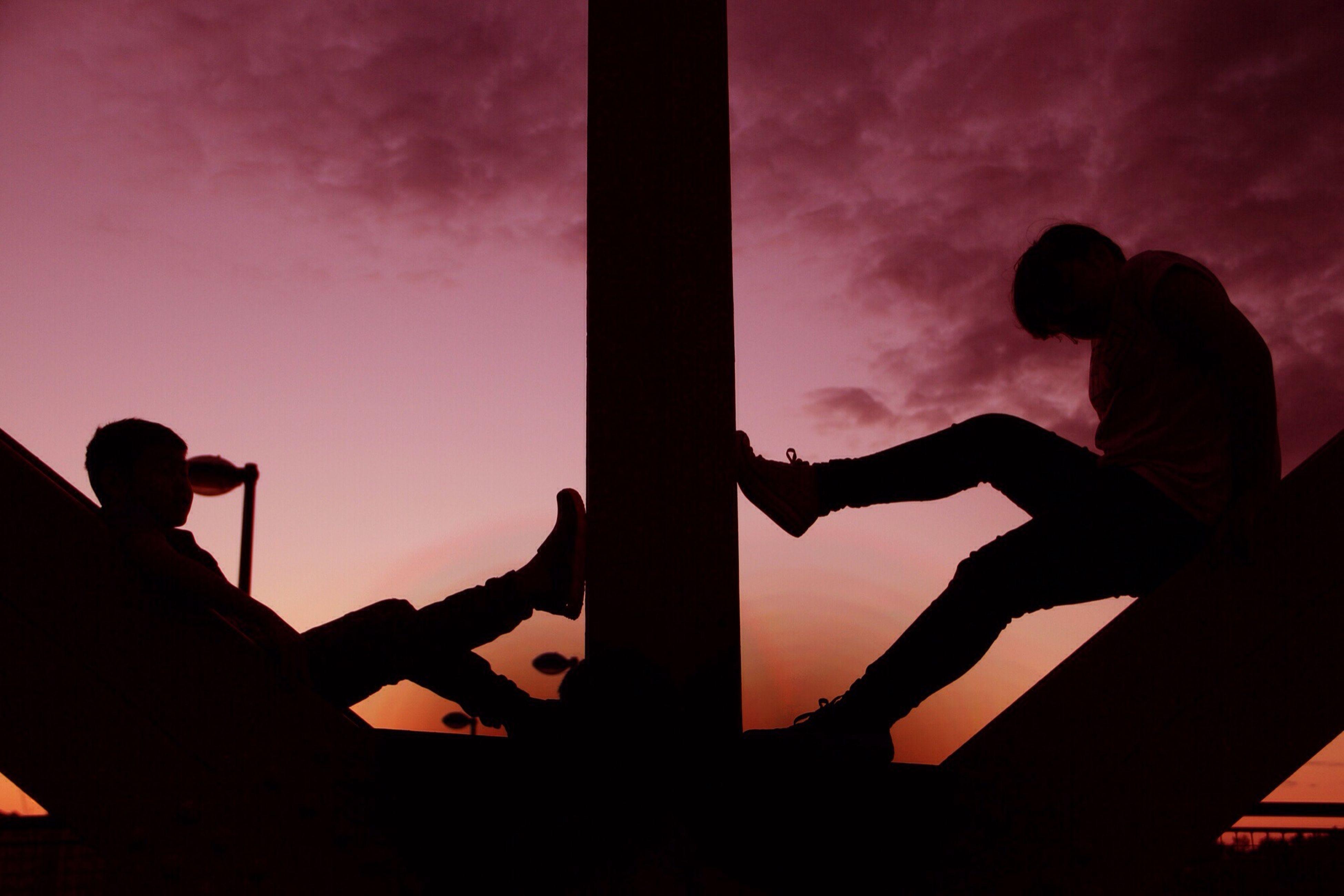 silhouette, sky, sunset, cloud - sky, low angle view, lifestyles, leisure activity, men, standing, cloud, cloudy, orange color, three quarter length, outline, dusk, person, dramatic sky