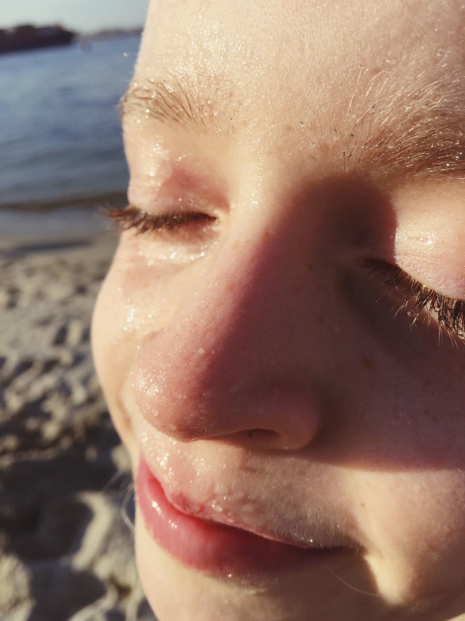 Close-Up Of Girl With Wet Face At Beach On Sunny Day