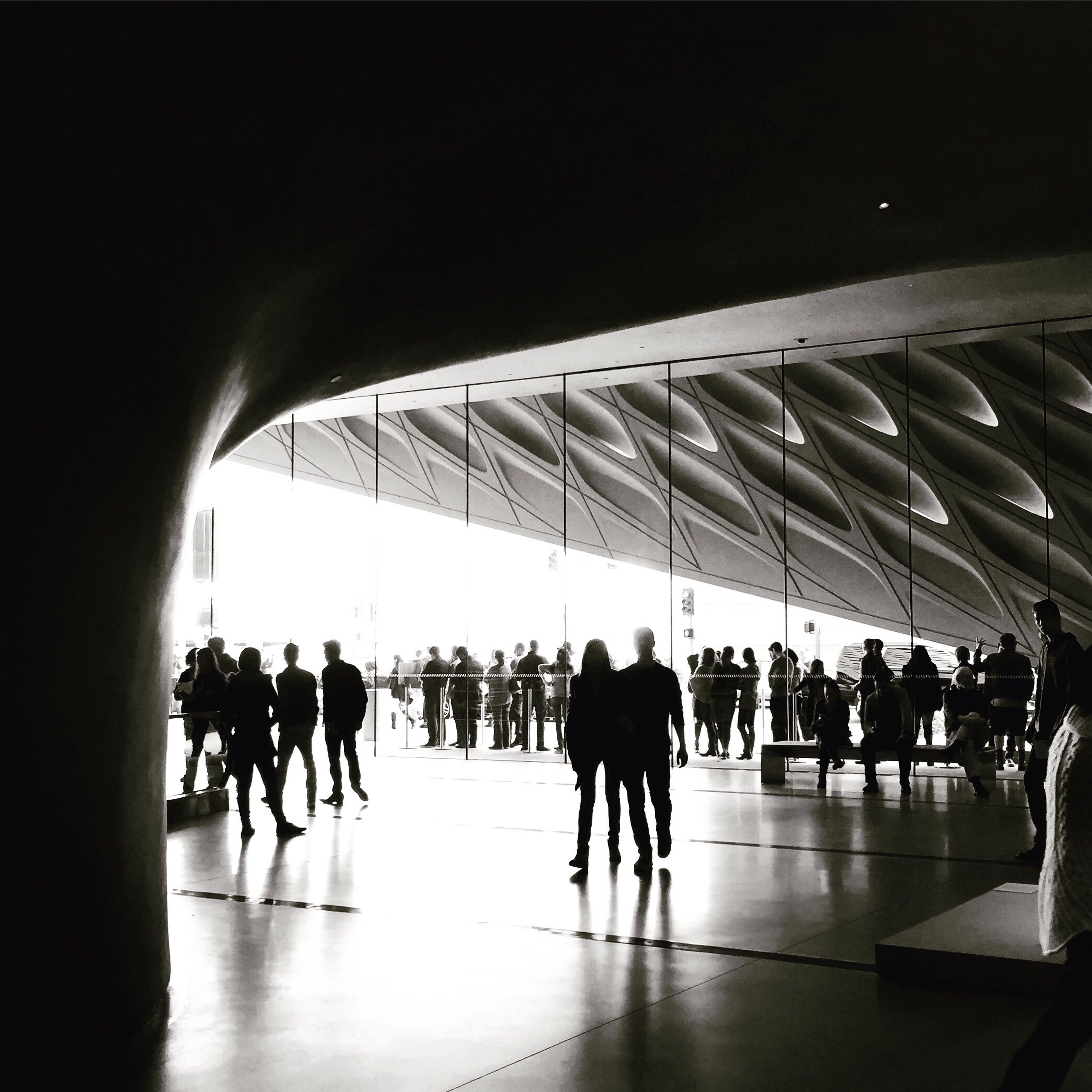 indoors, large group of people, architecture, built structure, men, person, walking, ceiling, lifestyles, city life, modern, travel, group of people, city, flooring, medium group of people, silhouette, full length, shopping mall