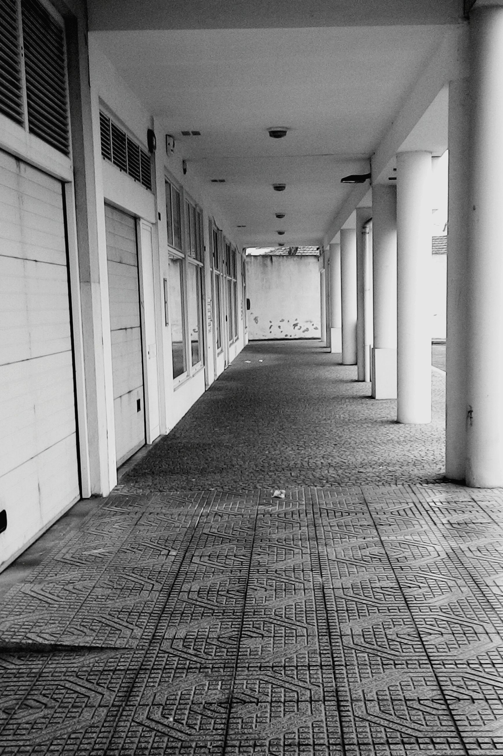 architecture, indoors, corridor, built structure, the way forward, ceiling, flooring, diminishing perspective, empty, tiled floor, building, absence, in a row, narrow, vanishing point, wall - building feature, walkway, architectural column, long, floor