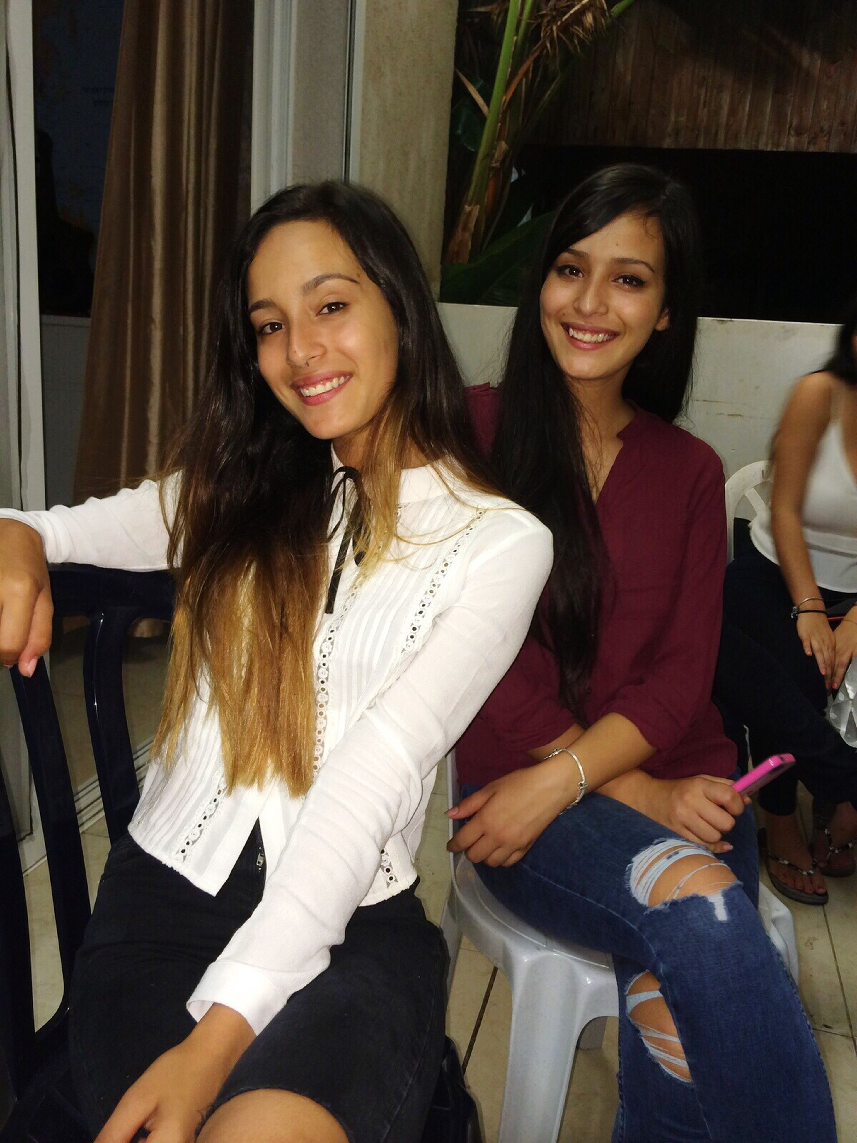 young adult, lifestyles, person, young women, portrait, leisure activity, looking at camera, smiling, casual clothing, happiness, sitting, front view, togetherness, long hair, three quarter length, indoors