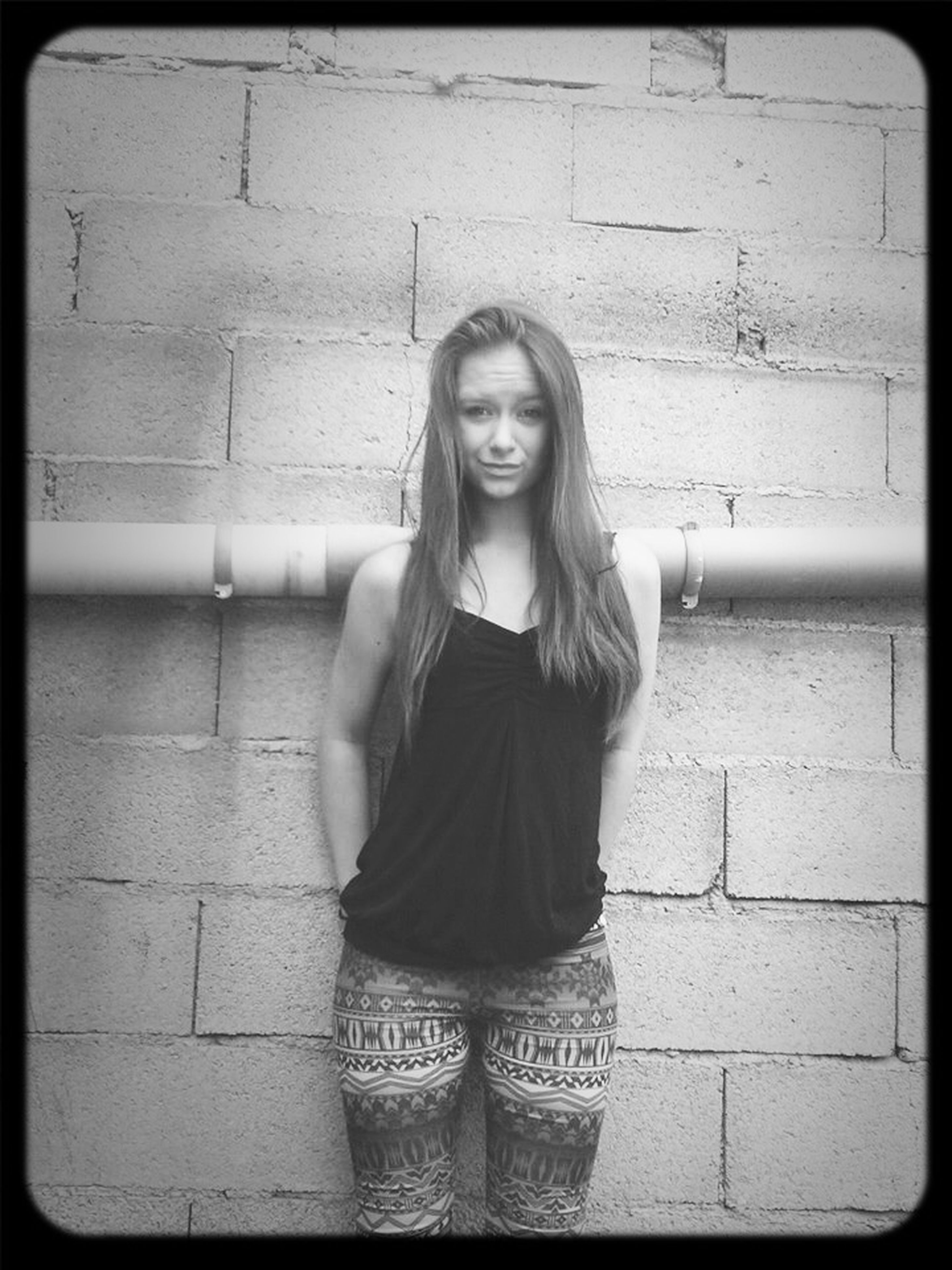 young adult, person, lifestyles, portrait, casual clothing, standing, looking at camera, front view, transfer print, young women, leisure activity, wall - building feature, waist up, three quarter length, long hair, auto post production filter, brick wall