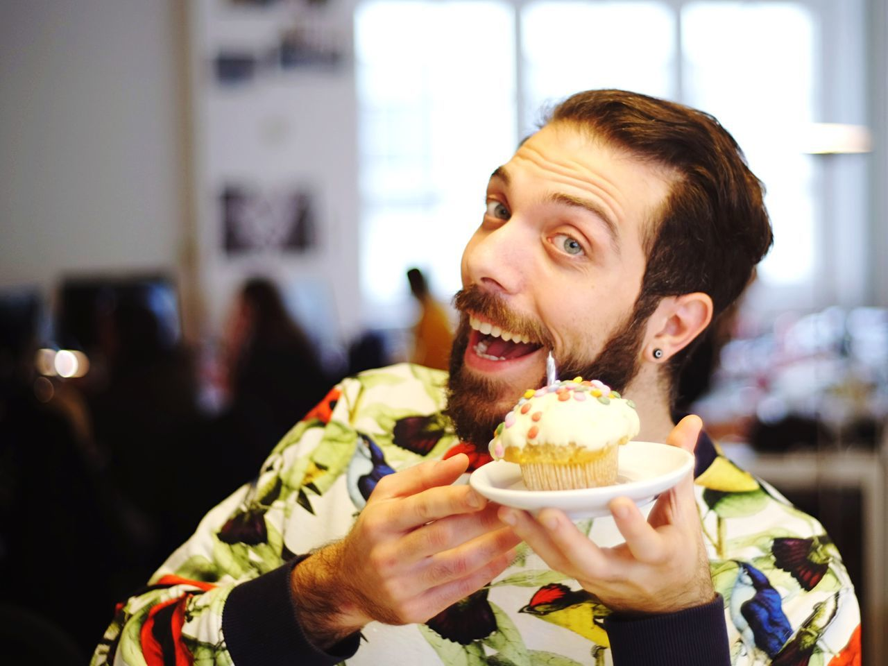 Portrait Of Cheerful Young Man Holding Cupcake During Birthday