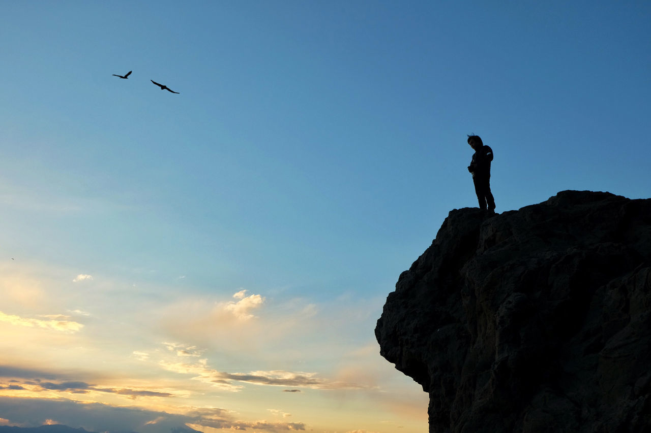 Silhouette Man Standing On Rock Against Blue Sky