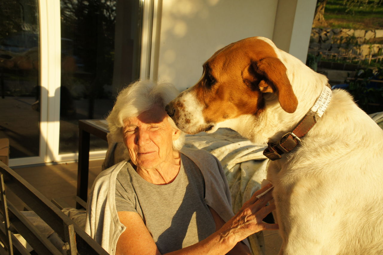 Senior Woman With Dog Sitting In Front Of House