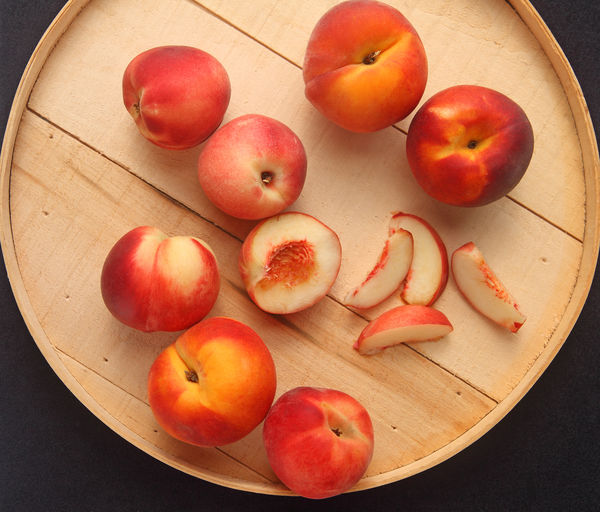 Peaches on a cheese box lid Fresh Produce Healthy Eating; Natural Light Red Textures Beige Tones Box Lid Close-up Day Directly Above Food Fresh Fruit Fruit Pieces Healthy Eating Indoors  No People Overhead Peaches Seasonal Several Snacks Still Life Unpeeled