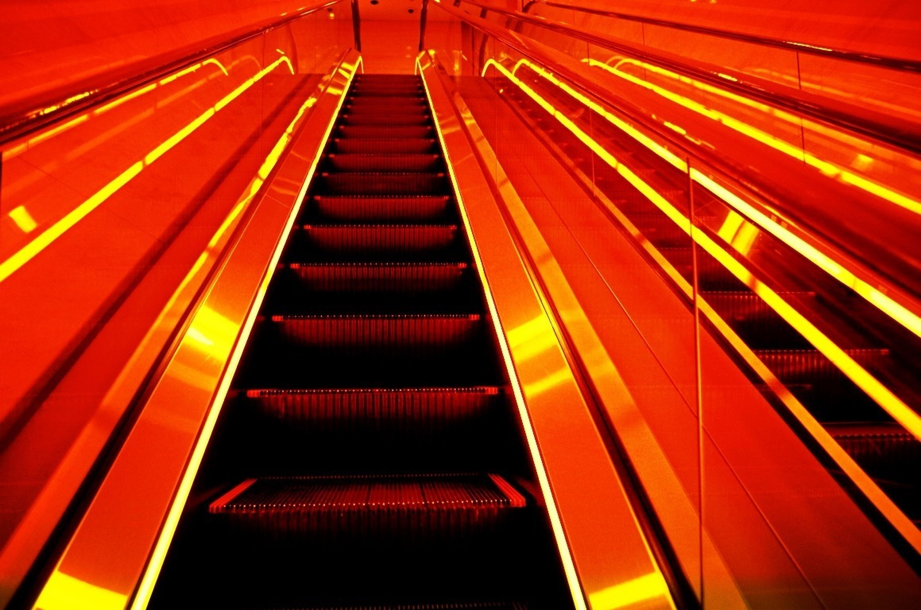 illuminated, the way forward, steps and staircases, steps, diminishing perspective, modern, indoors, built structure, staircase, railing, architecture, low angle view, escalator, pattern, orange color, vanishing point, no people, red, empty, high angle view