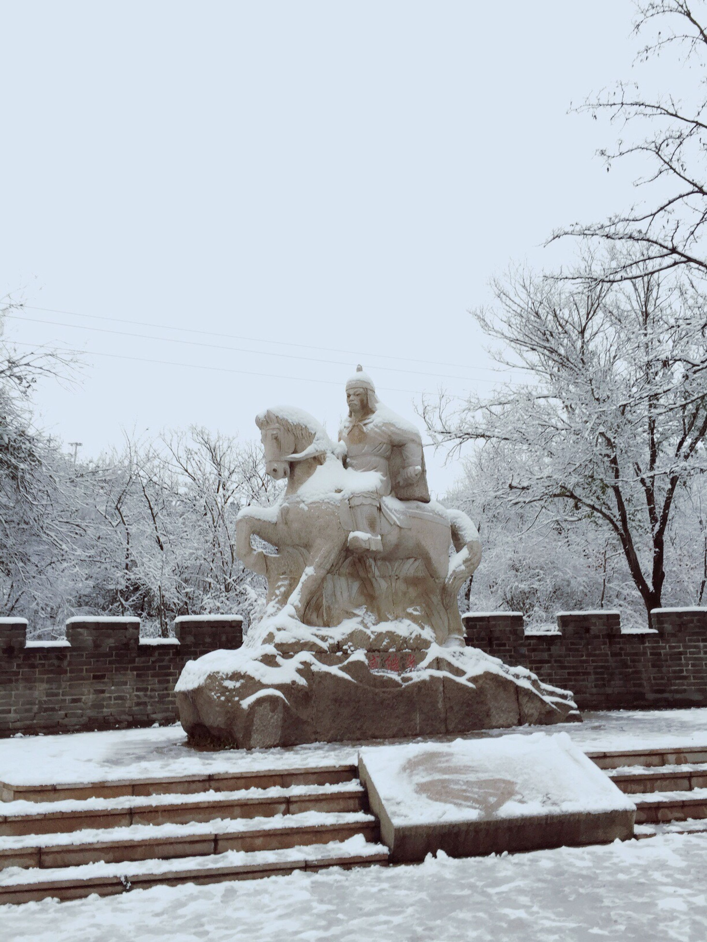 statue, human representation, sculpture, art and craft, art, creativity, tree, clear sky, winter, snow, animal representation, cold temperature, religion, stone material, cemetery, day, built structure, bare tree