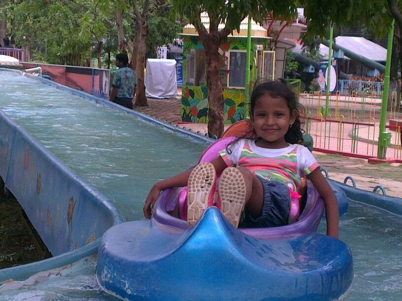 childhood, smiling, looking at camera, real people, happiness, front view, one person, portrait, playground, outdoors, leisure activity, tree, day, lifestyles, full length, sitting, playing, water, people
