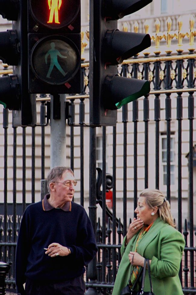 """""""I swear we're going in circles!"""" Talking Concerned Standing Casual Clothing Focus On Foreground Older Couple Traffic Light  City Street Talking Smoking"""