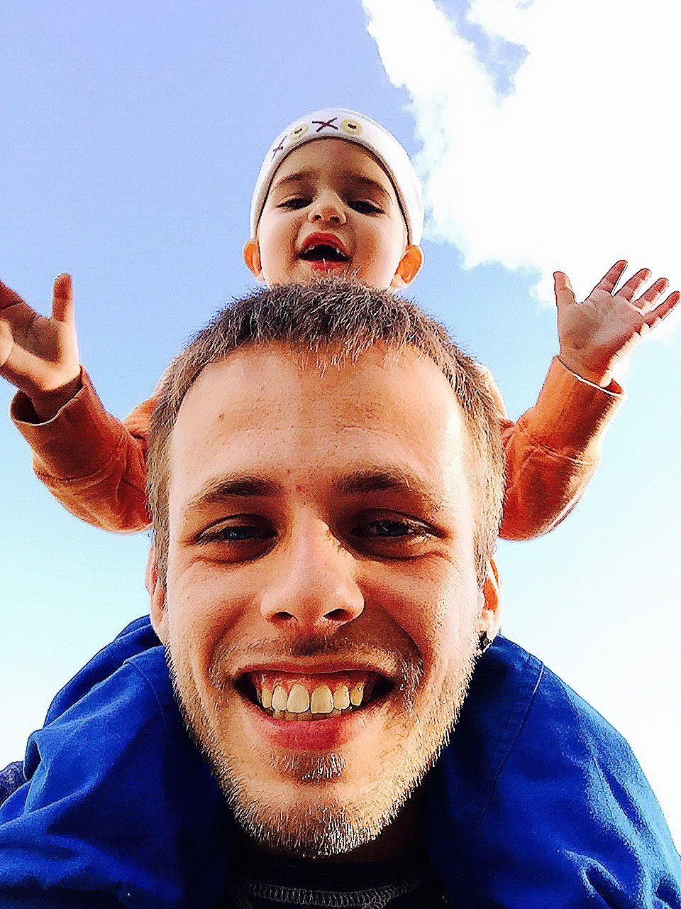 childhood, smiling, portrait, looking at camera, happiness, front view, real people, sky, day, leisure activity, boys, low angle view, headshot, fun, elementary age, one person, gesturing, lifestyles, cheerful, outdoors, making a face, blue, close-up, clear sky, blond hair, young adult, people