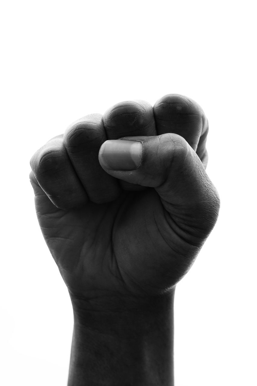 Close-Up Of Hand Clenching Fist Against White Background