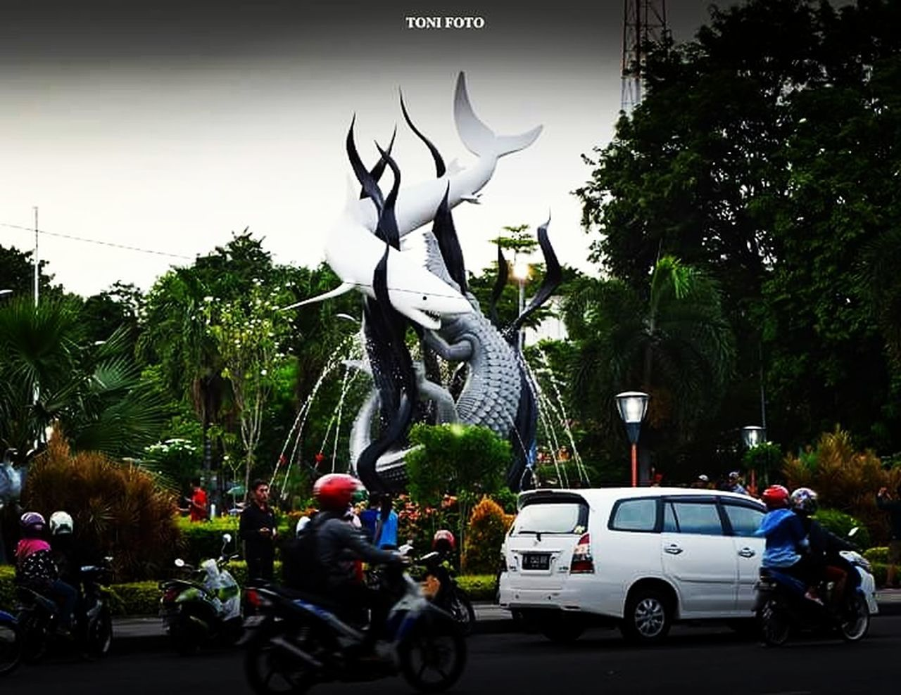 car, tree, land vehicle, statue, transportation, mode of transport, sculpture, day, road, outdoors, no people, sky