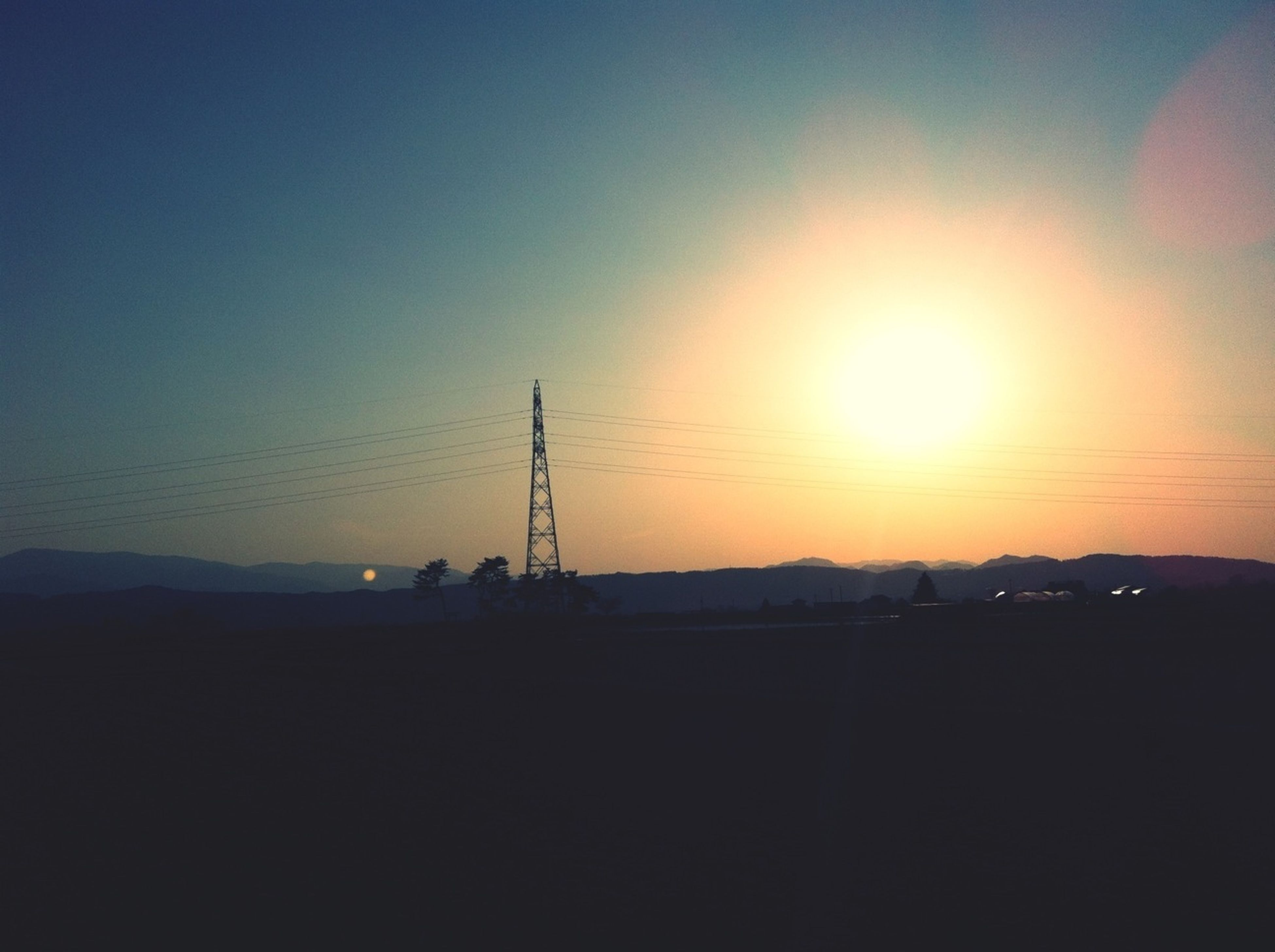 sunset, silhouette, sun, orange color, copy space, clear sky, scenics, tranquility, tranquil scene, beauty in nature, landscape, nature, electricity pylon, sunlight, fuel and power generation, sky, idyllic, outdoors, technology, electricity