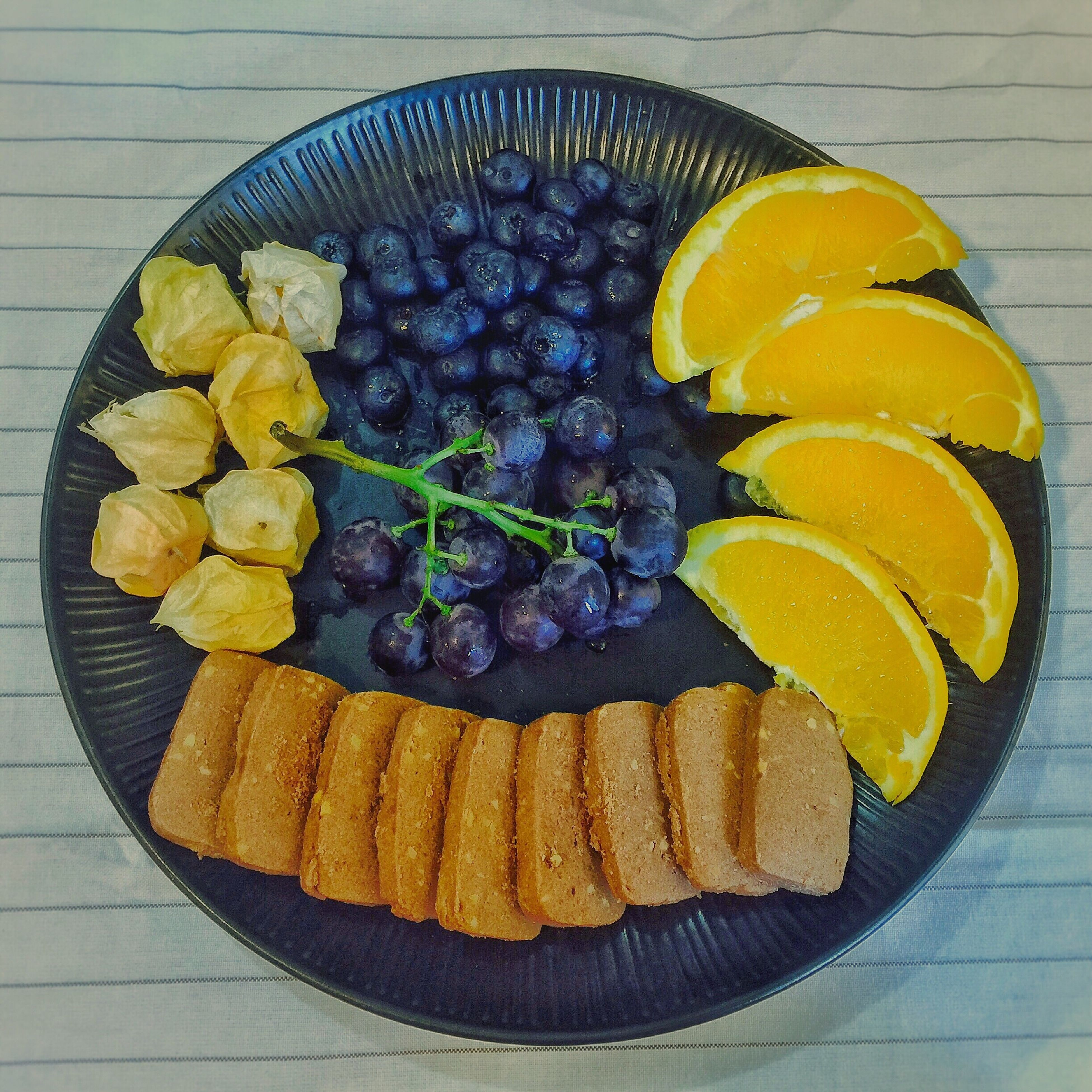food and drink, fruit, yellow, food, healthy eating, freshness, indoors, directly above, citrus fruit, slice, serving size, vibrant color, large group of objects, blue, fruit salad, cross section, bunch, multi colored, indulgence