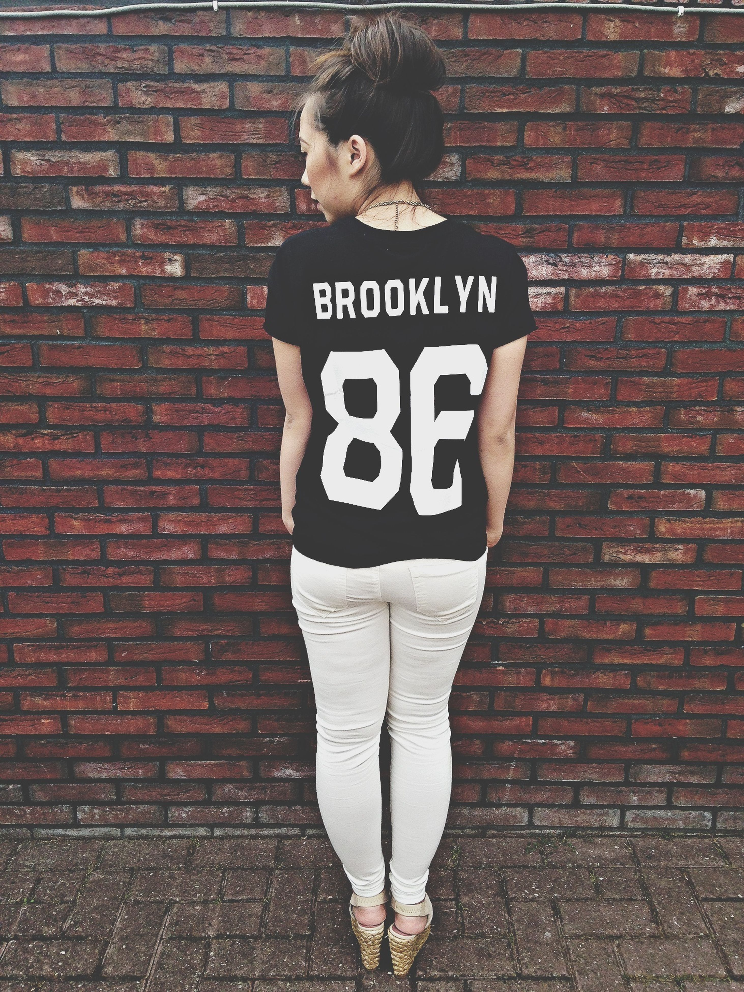 text, brick wall, western script, communication, wall - building feature, built structure, architecture, building exterior, front view, red, wall, standing, day, outdoors, person, lifestyles, casual clothing, sign