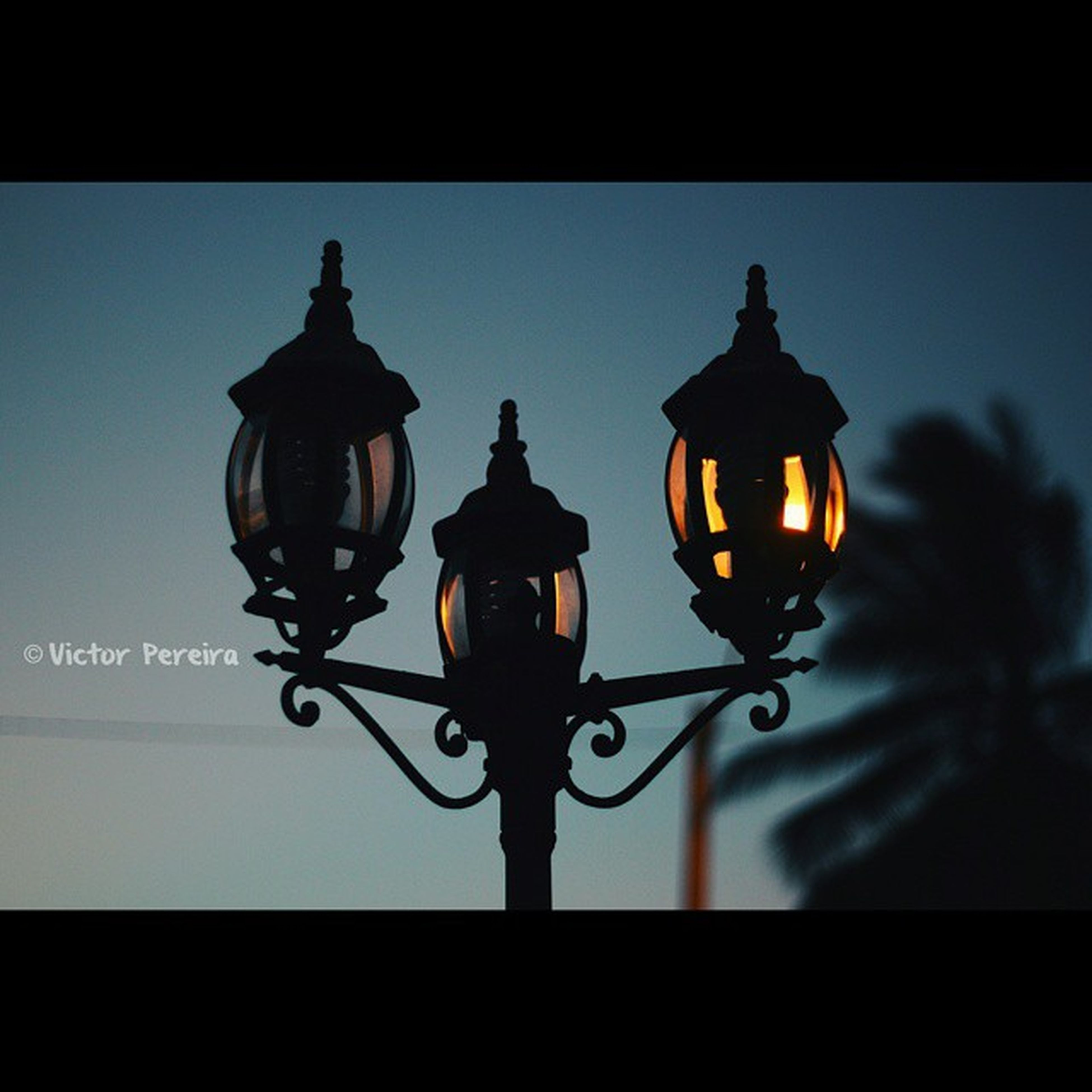 lighting equipment, illuminated, street light, low angle view, silhouette, electricity, transfer print, hanging, electric lamp, electric light, light bulb, clear sky, lantern, sky, auto post production filter, built structure, metal, night, indoors, dusk