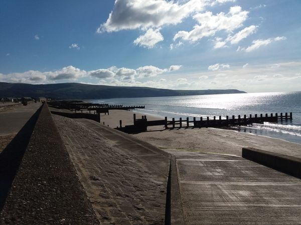 Barmouth seafront Sea Wall Shimmering Sea Beach Beauty In Nature Blue Sky Day Groynes Horizon Over Water Mountains Nature No People Outdoors Sand Scenics Sea Sky Sunlight Tranquility Water