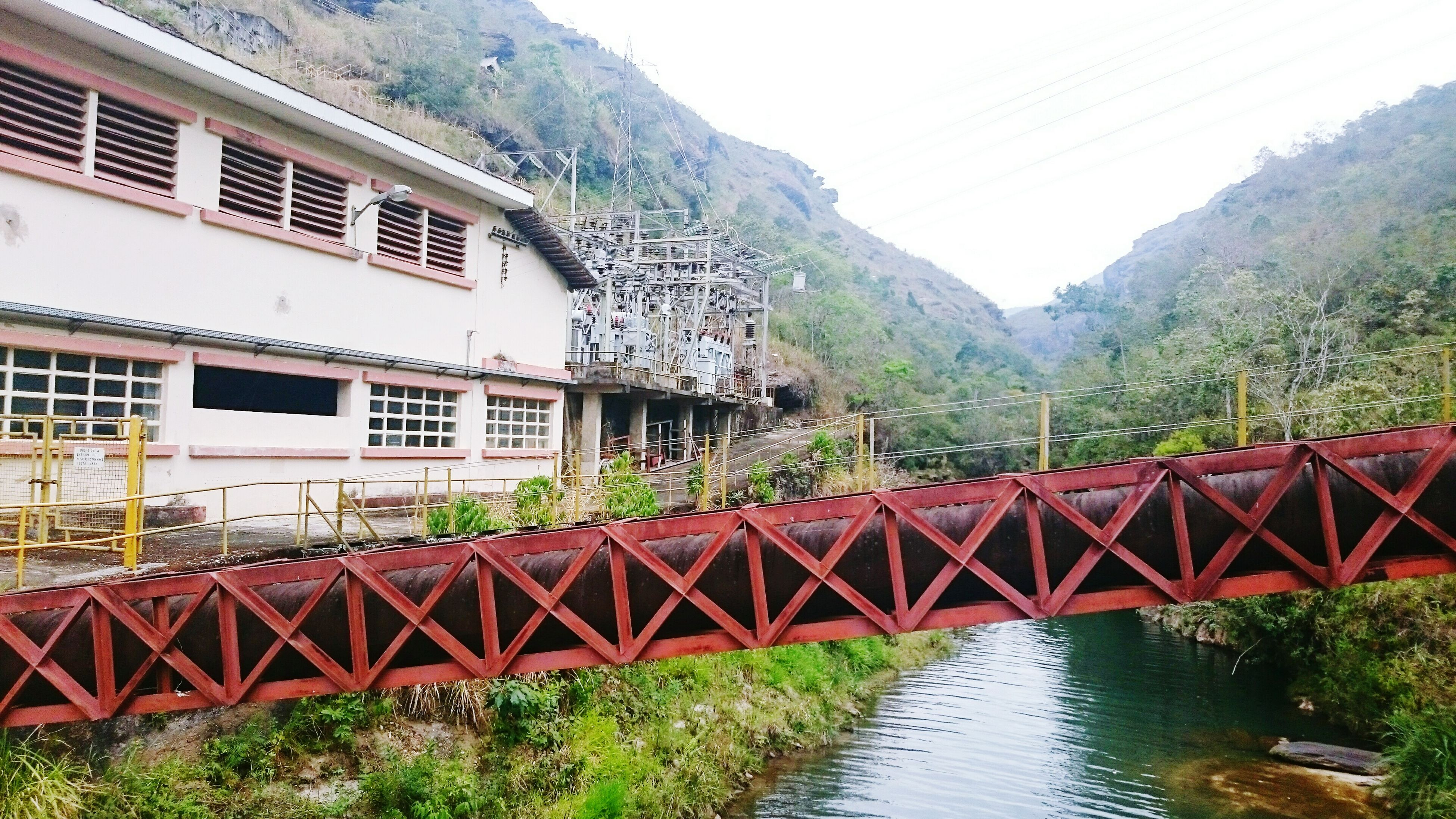 architecture, built structure, water, building exterior, railing, connection, bridge - man made structure, canal, mountain, river, tree, footbridge, house, clear sky, day, bridge, residential structure, waterfront, plant, nature