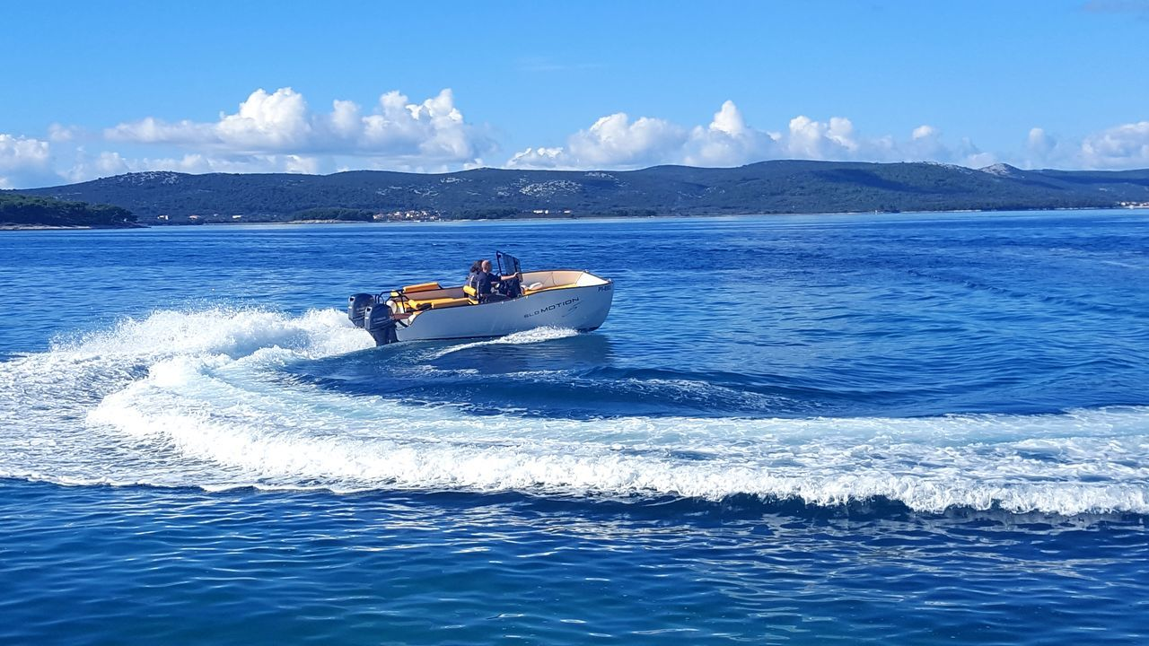Nautical Vessel Adventure Aquatic Sport People Sea Outdoors Horizontal Person One Person Day Adult Cityscape Catamaran Nature Yachting Sailboat Clear Sky Mountain Water Blue Sunny Beauty In Nature Cloud - Sky