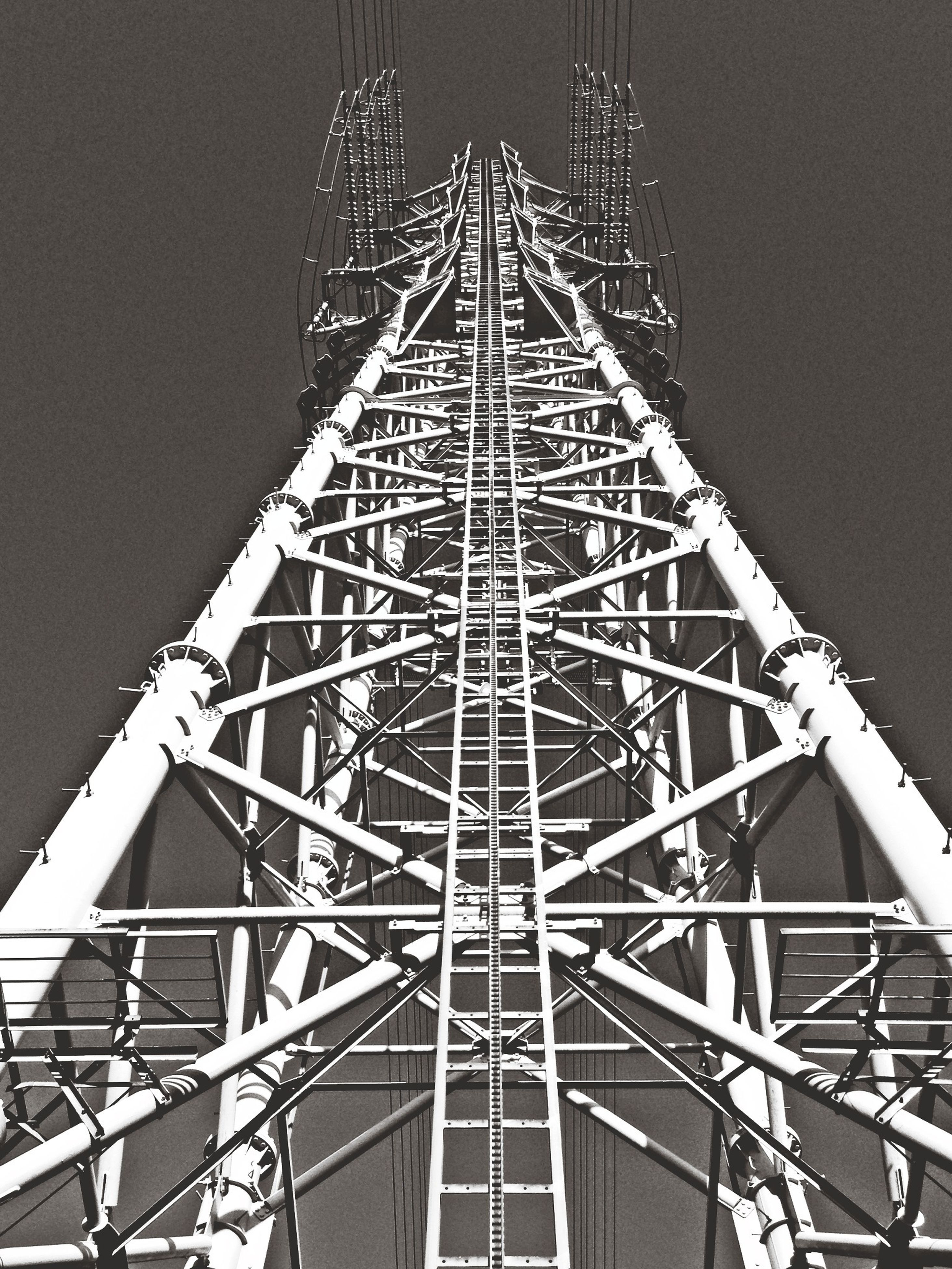 low angle view, clear sky, built structure, architecture, metal, tall - high, sky, metallic, connection, no people, outdoors, diminishing perspective, tower, copy space, day, technology, dusk, electricity, tall