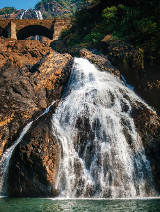 Beautiful view of the Dudhsagar waterfall. The largest waterfall in Goa, India Beauty In Nature Blurred Motion Bridge Dudhsagar Falling Water Flowing Goa India Landscape_Collection Long Exposure Motion Mountain Natural Landmark Non-urban Scene Power In Nature Purity Rock - Object Stream View Water Waterfall