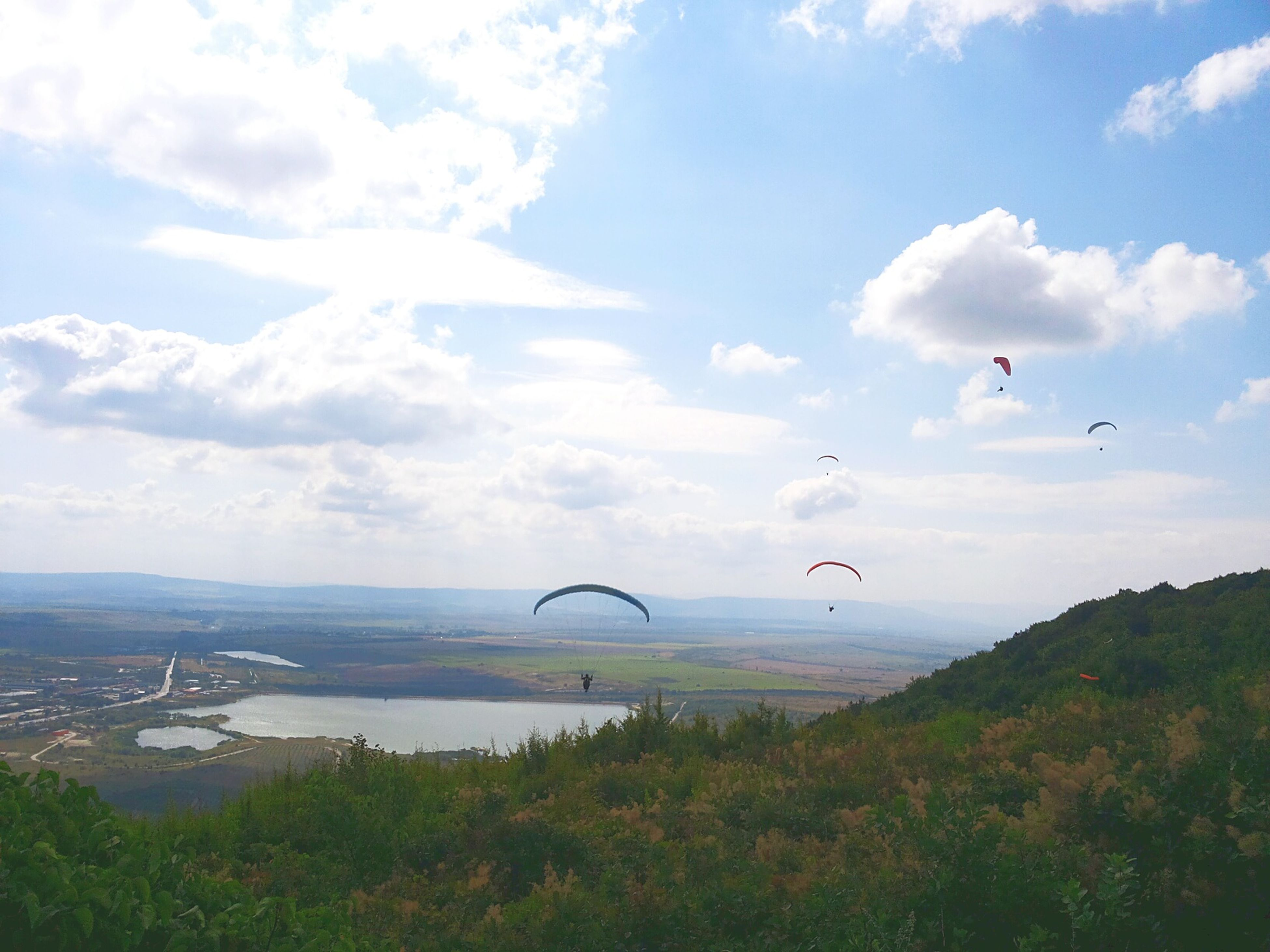 flying, sky, mid-air, parachute, paragliding, cloud - sky, scenics, extreme sports, leisure activity, adventure, beauty in nature, nature, tranquility, tranquil scene, mountain, freedom, landscape, cloud