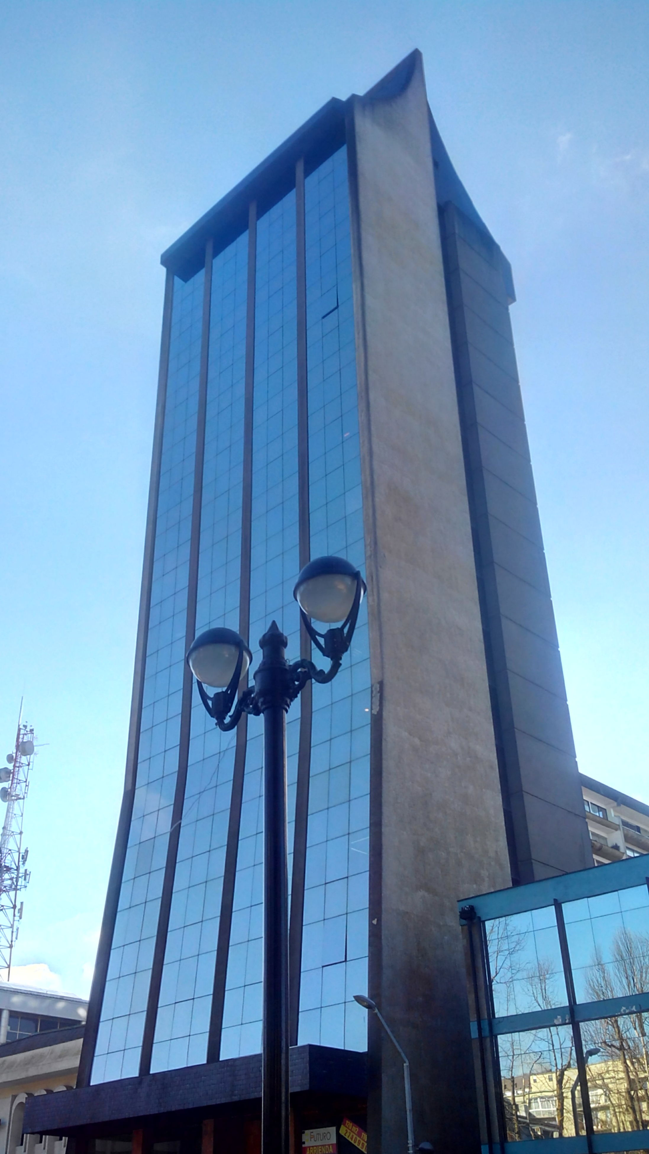 low angle view, building exterior, architecture, built structure, city, building, street light, office building, sky, tall - high, clear sky, modern, blue, tower, skyscraper, day, outdoors, no people, sunlight, glass - material